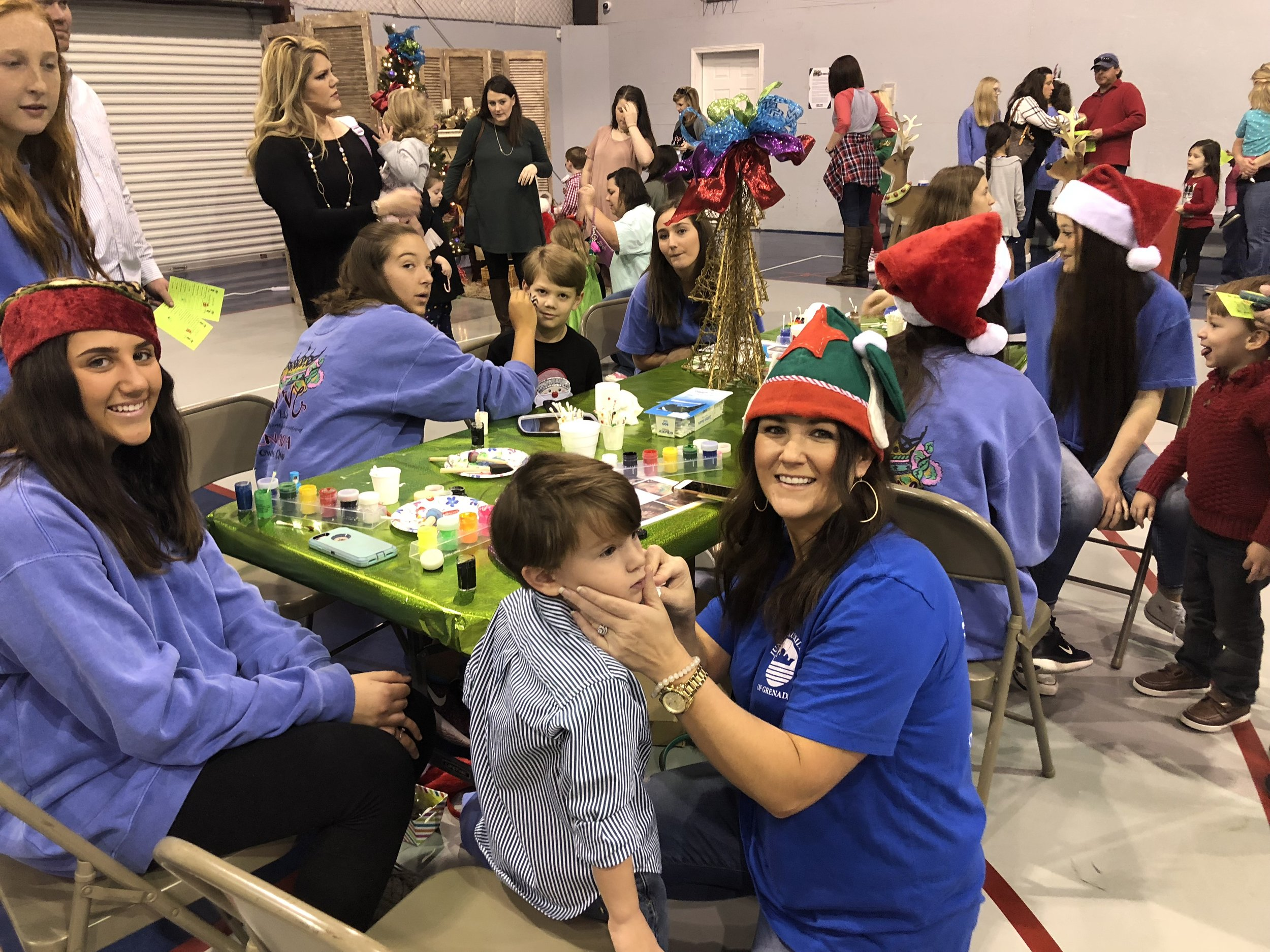 The Crown Club committee members and Crown Club members painting faces while serving at Snacks with Santa.