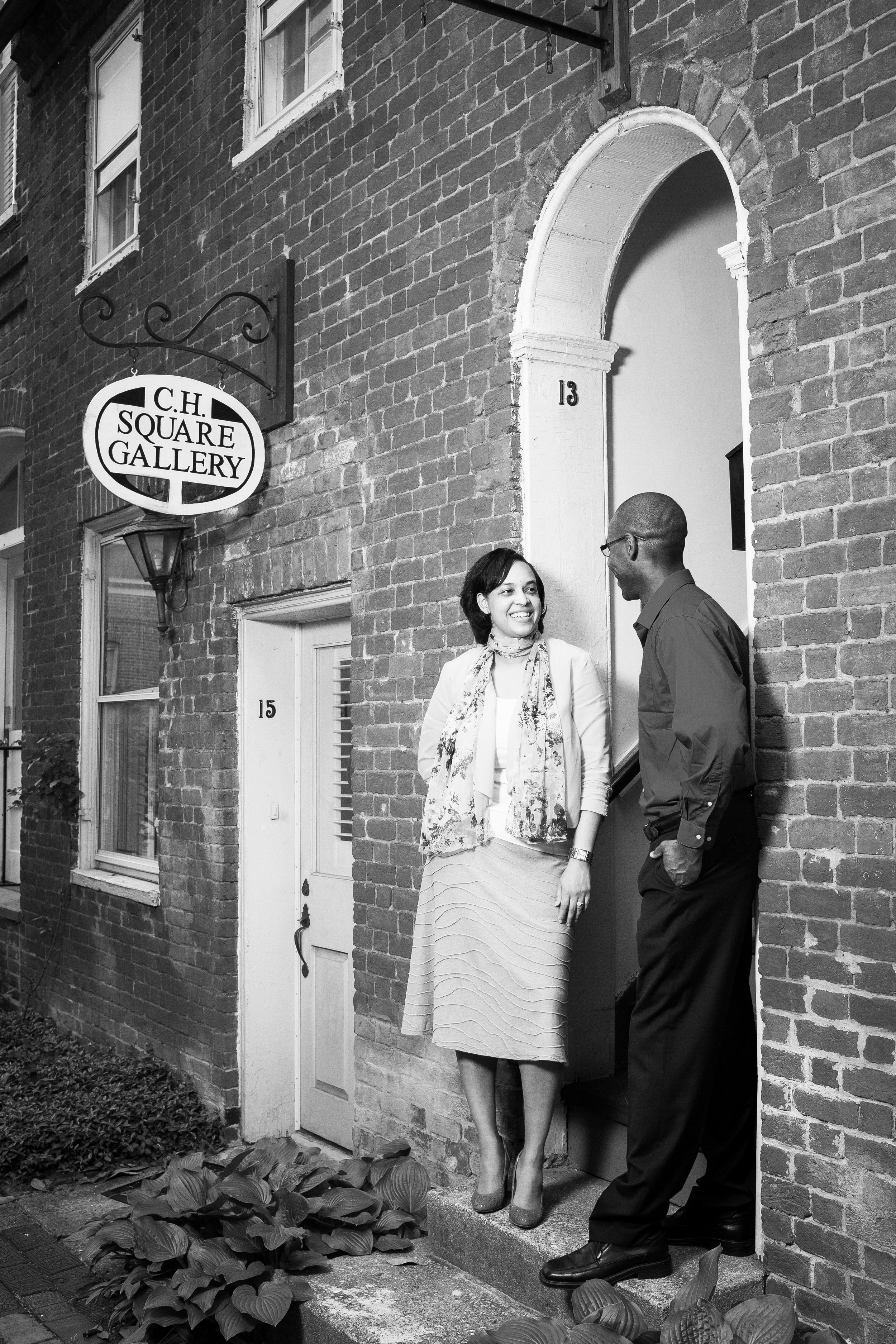 Black and white engaged couple in front of brick