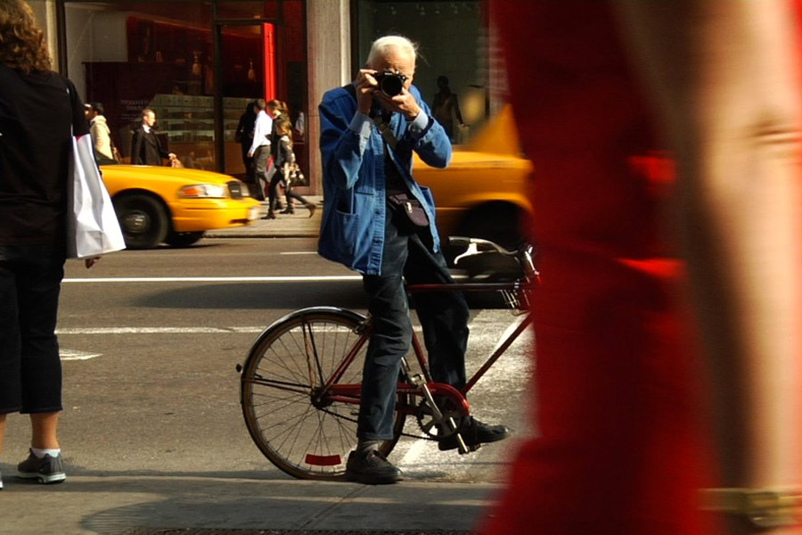 L: Bill Cunningham, working. ©  First Thought Films.  R: Paul Newman,  working . © Warner Bros. Ent.