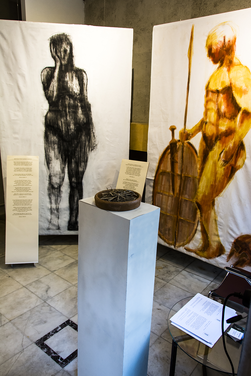 Penelope (compressed charcoal on canvas) on the left, Achaean warrior (pigment and glue on canvas) on the right at Tasarım Bakkalı. Soil from Troy on the foreground.