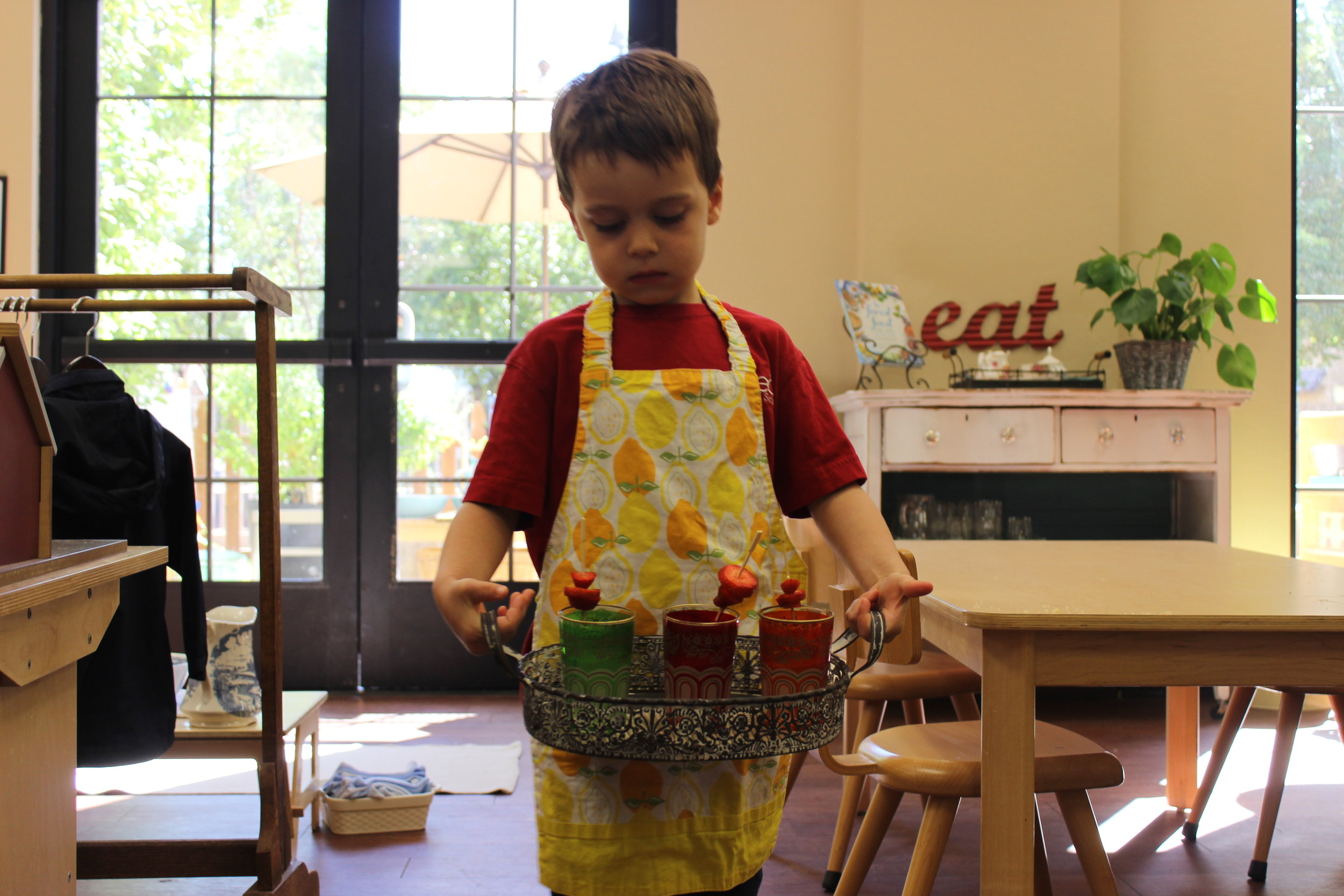 Carrying his fresh squeezed lemonade garnished with strawberries to serve to the office staff.