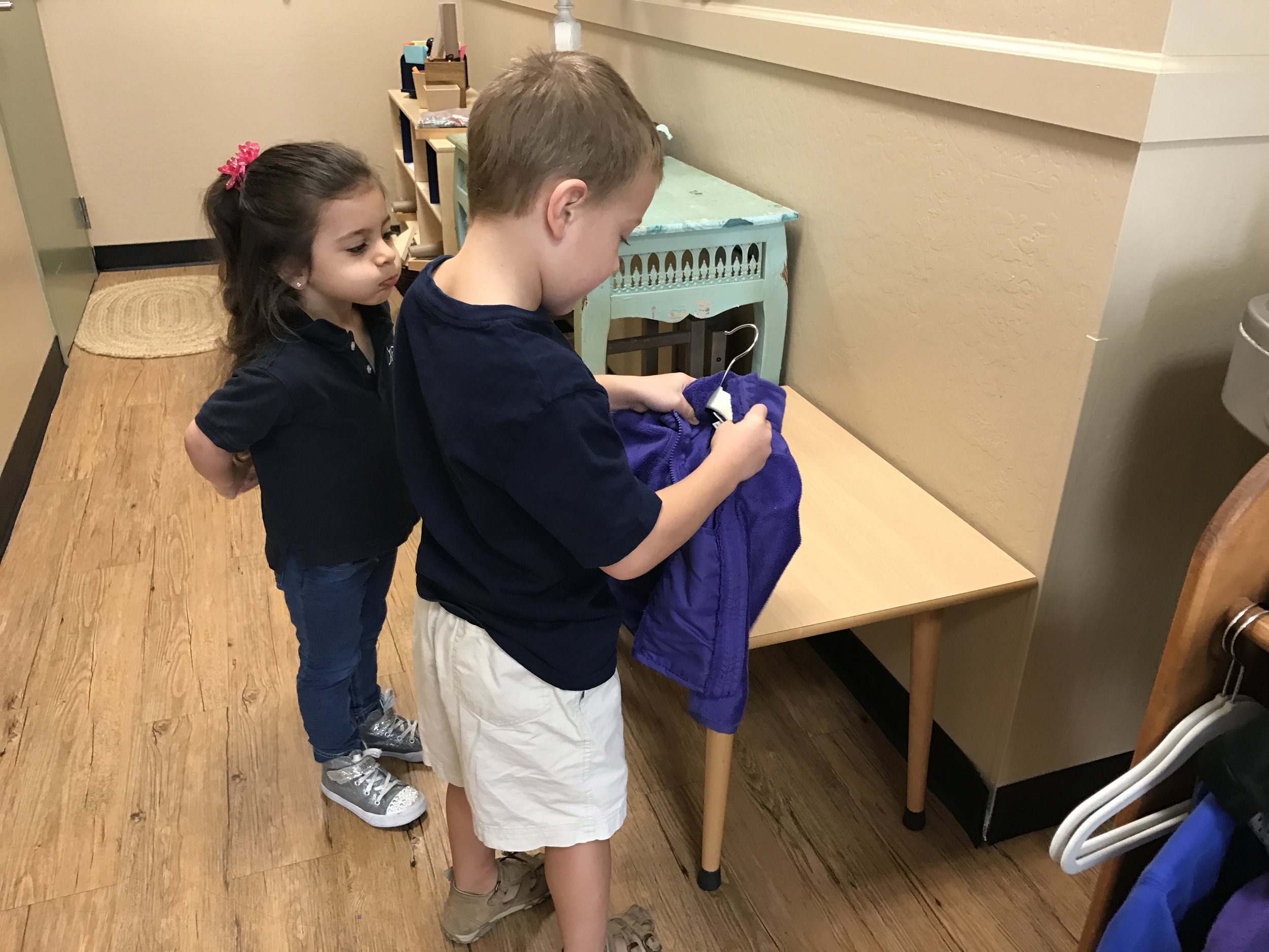 An older child helping his younger friend to hang her coat.