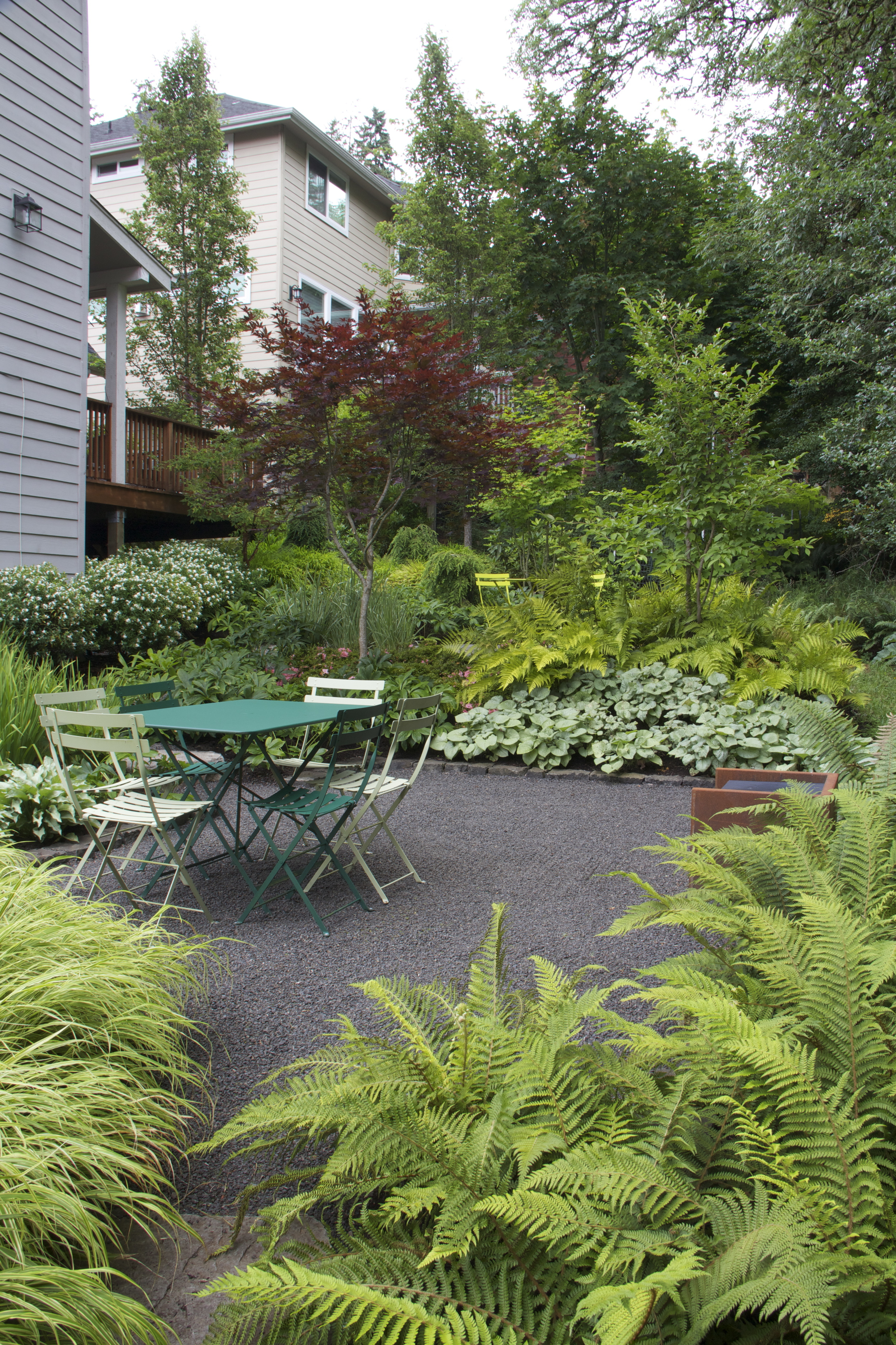 Layered plantings and a gentle slope separate the nearby seating areas.