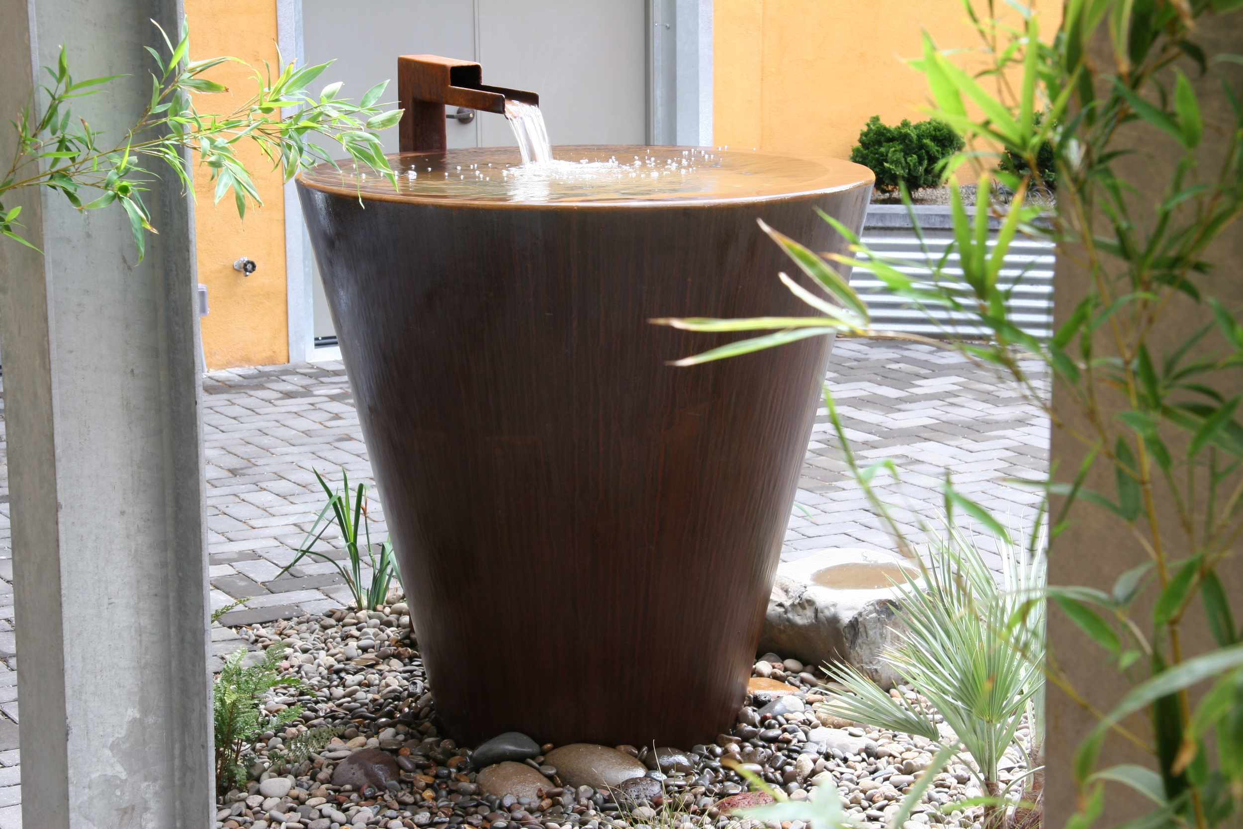 A rusty corten steel fountain, designed by Mosaic Gardens.