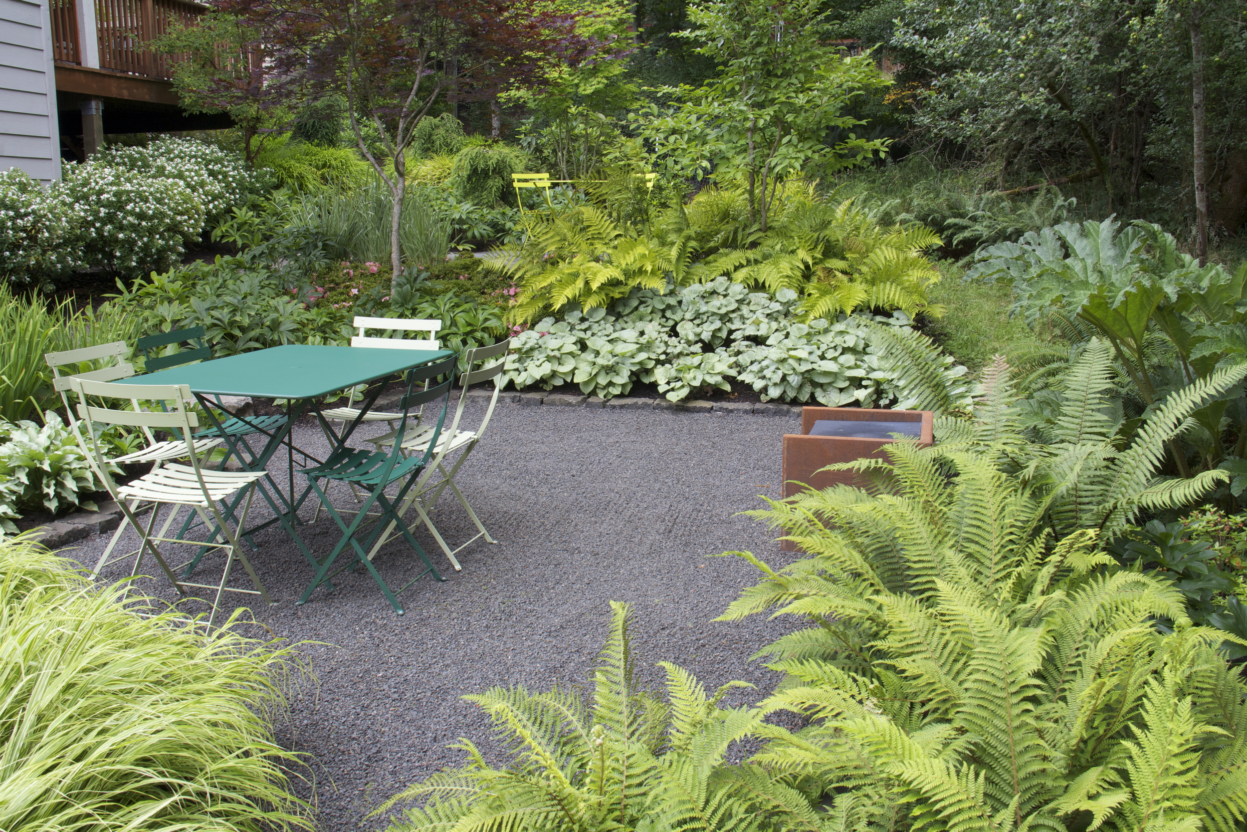 Quarter minus gravel is a soft, low maintenance and lower cost option for a path or terrace.  Its dark gray color looks quite at home in this shady, northwest garden.