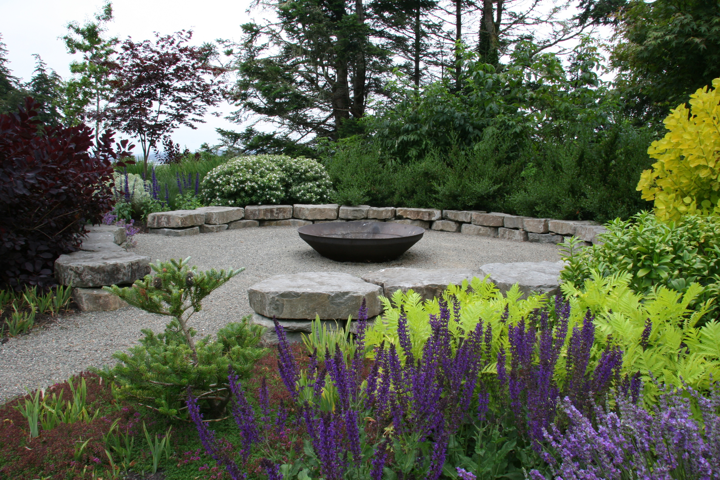 This 20' diameter circular, seating-height stone wall makes a fire pit for a crowd on the Oregon coast.
