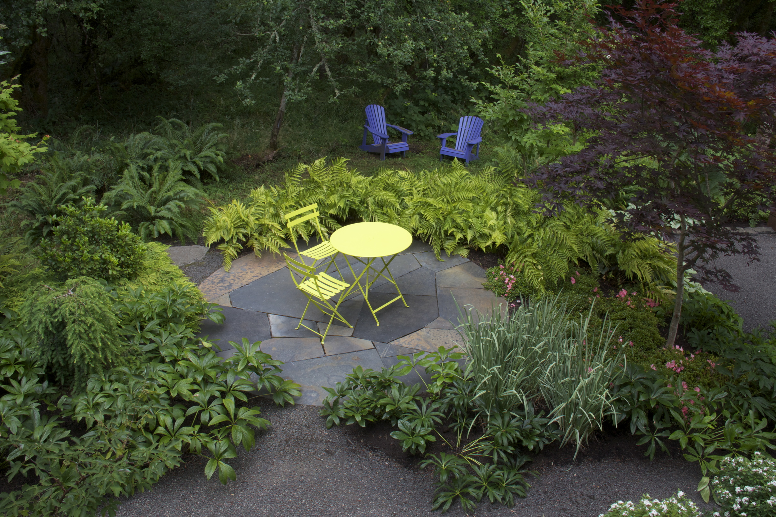 A circular terrace is the centerpiece of this shady space.