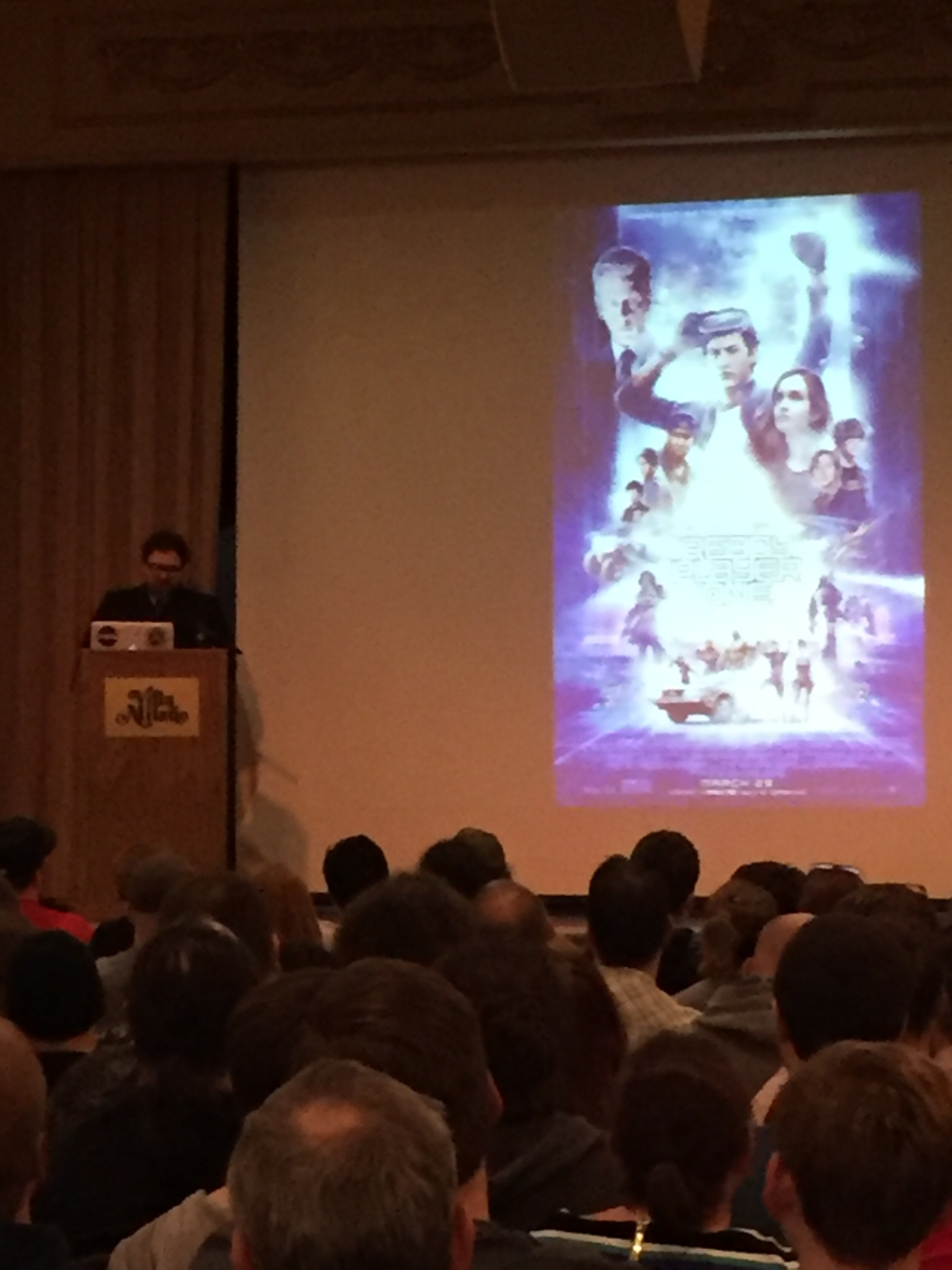 Pardon the shitty phone photography. [image description: Author Ernest Cline is standing behind a podium on stage talking about his life as an author and his most successful work, Ready Player One. The movie poster for Ready Player One is projected in the background.]