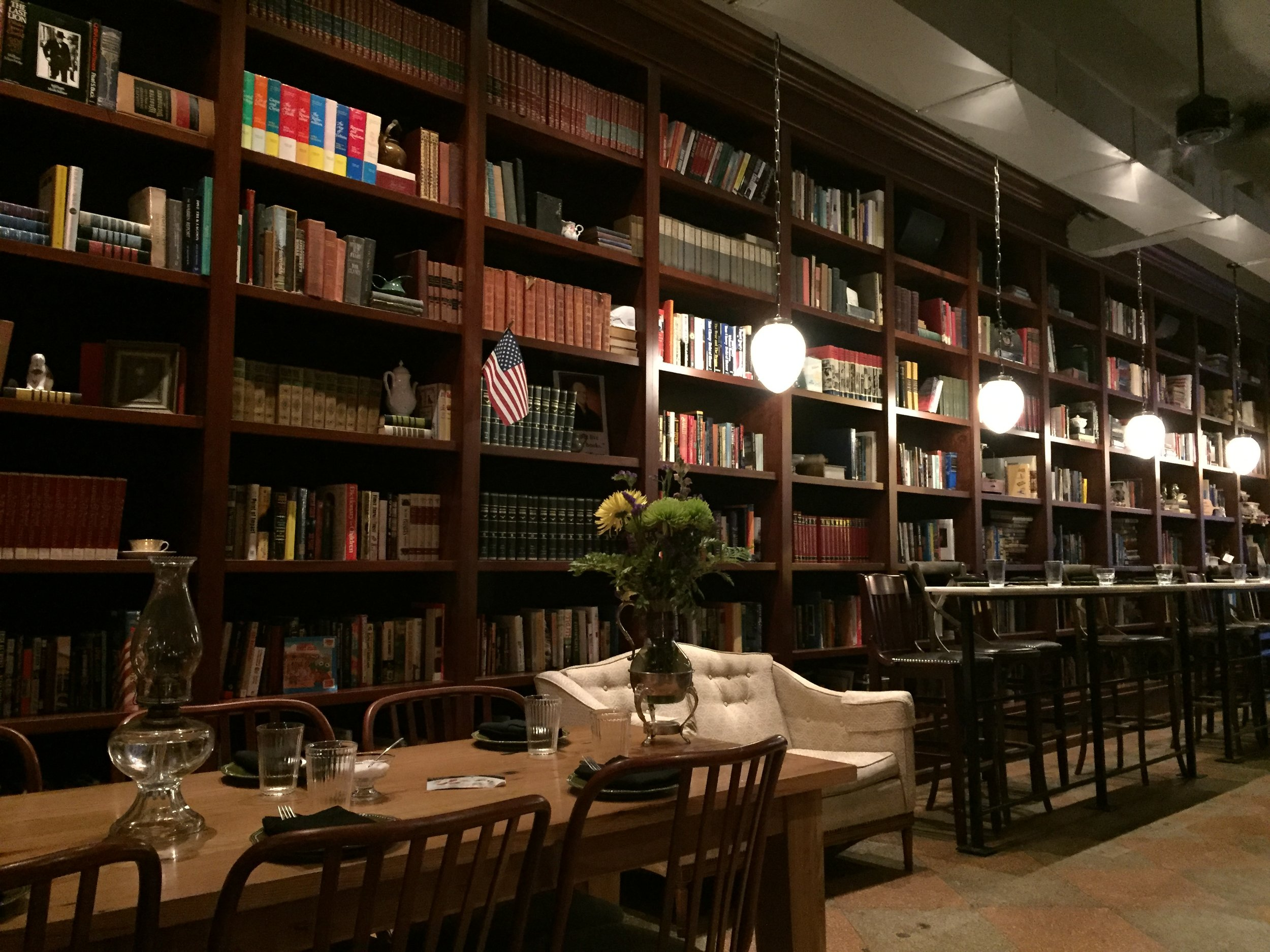 [image description: Inside the restaurant Asterisk Supper Club. There are floor-to-ceiling dark wood bookshelves packed with vintage encyclopedias and modern paperbacks alike. There are dangling orb lights, high top bar seating, long low table seating, and a white loveseat.]