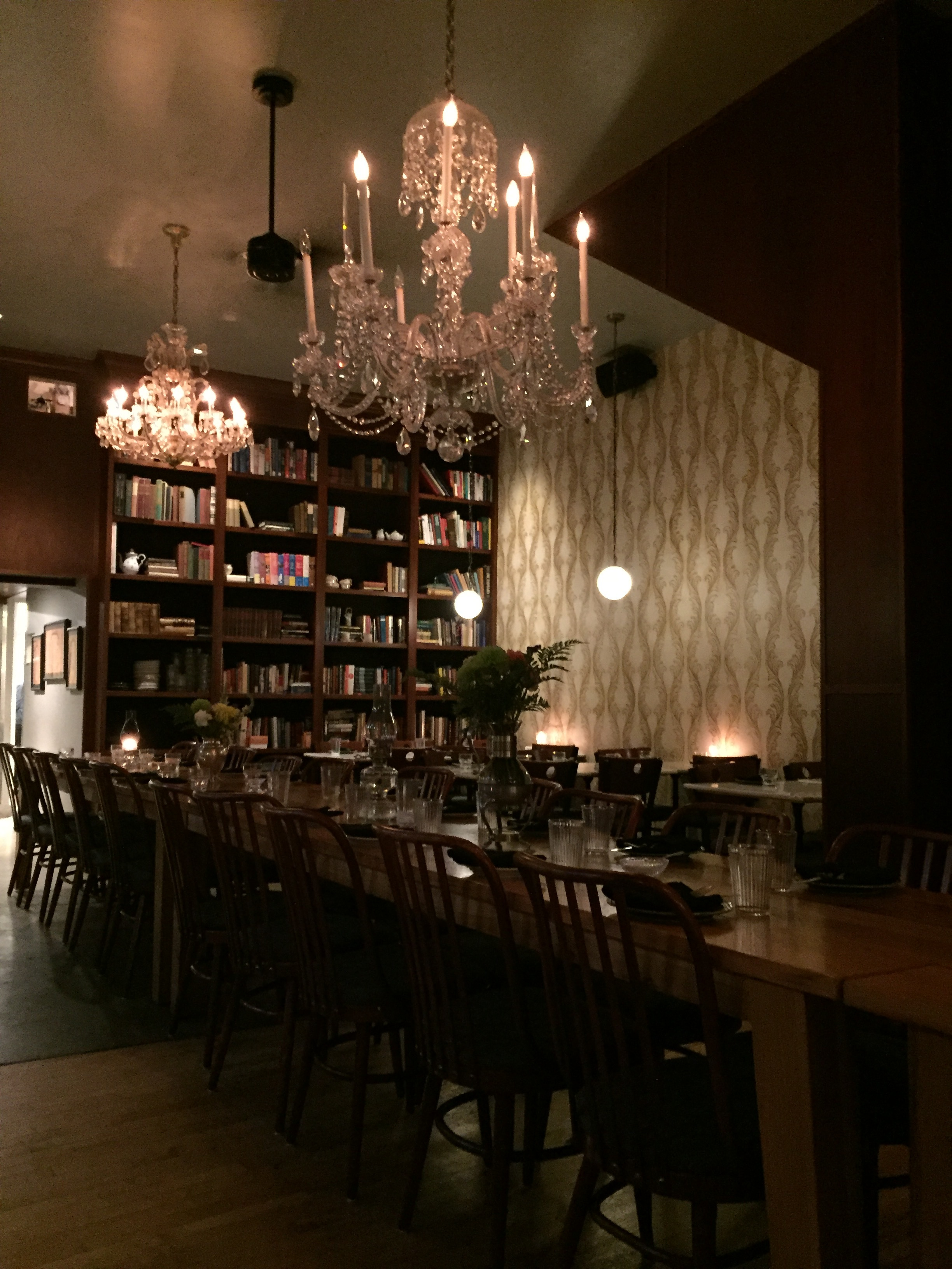 [image description: Inside Asterisk Supper Club. There's a long, picnic style table that could seat ~30 people. The table has vases with flowers on top, as well as clear glasses and small green plates. Behind the table are more floor-to-ceiling bookshelves. Dangling orb lights and large chandeliers hang overhead. The one wall that's not covered in books is a creamy white color with a repeating gold brocade design.]