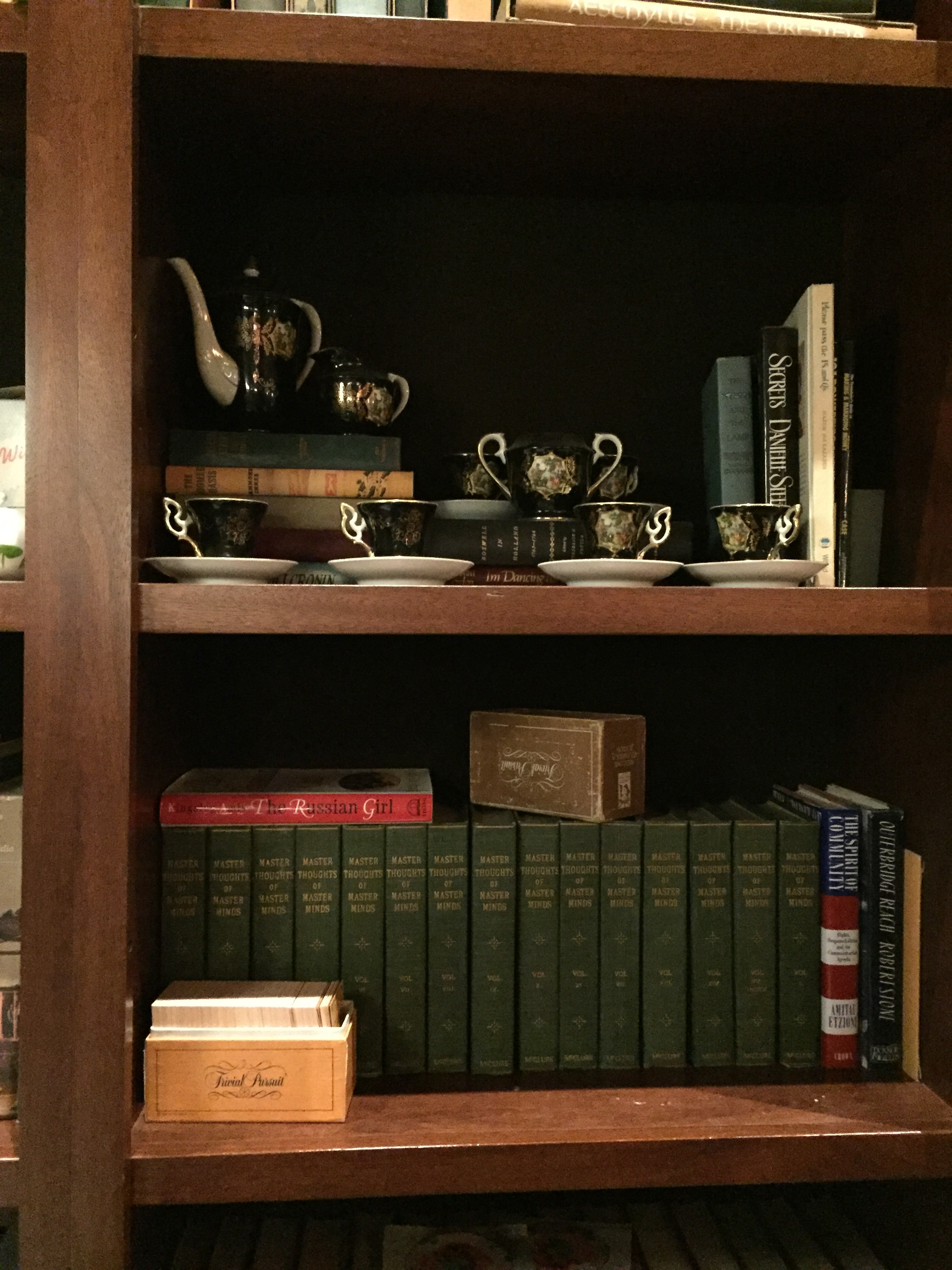 [image description: an up-close photo of one of Asterisk's bookshelves. There's a multi-volume set of books in dark green, two boxes of vintage Trivial Pursuit, and an elegant black and gold tea set.]