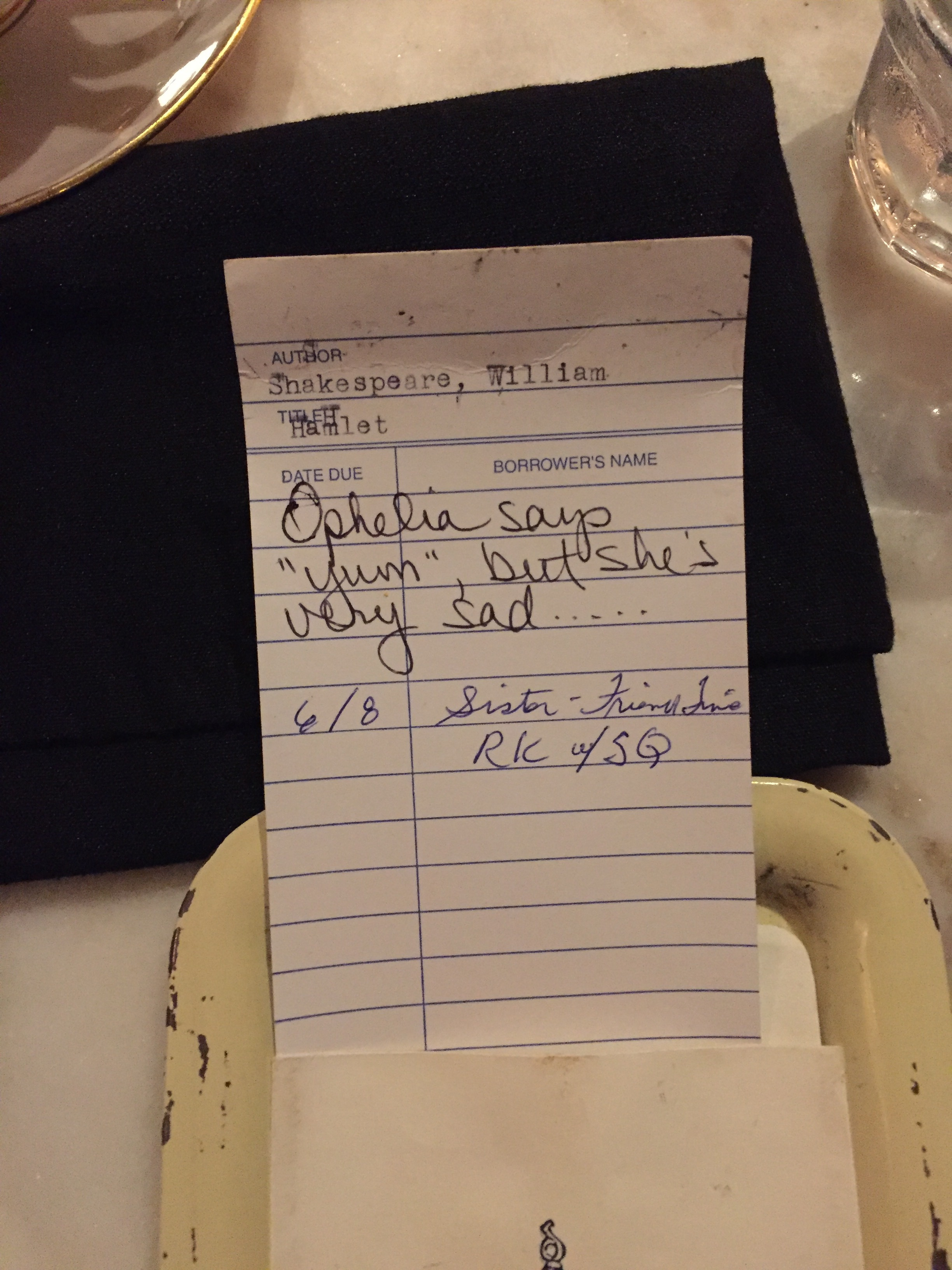 """[image description: a better look at the library checkout card. Someone has written """"Ophelia says 'yum' but she's very sad..."""" and another person has signed and dated the card. (The date is recent, so it's definitely a restaurant patron and not an old library patron.)]"""