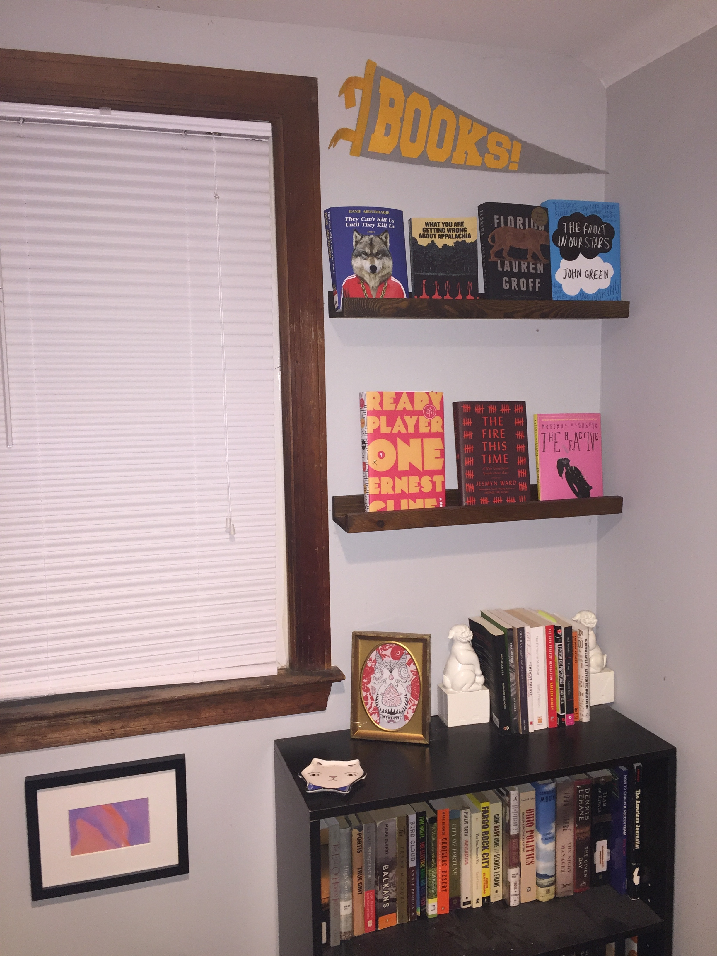 """[image description: a wall with a window, a small black bookshelf, and two display shelves with books facing outward. There are also two framed pieces of abstract art and a small triangular flag that says """"books.""""]"""