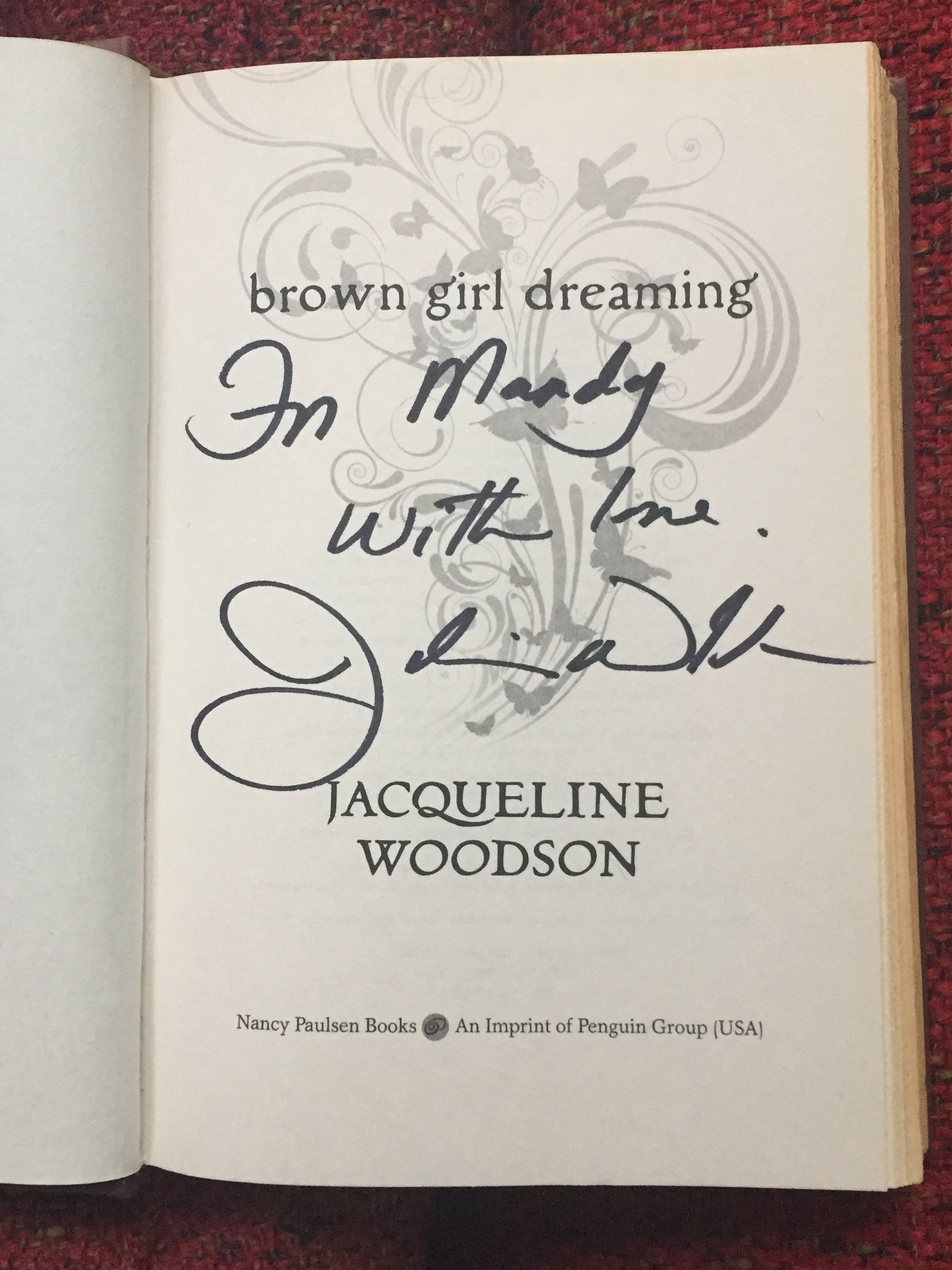 """[image description: My signed copy of Brown Girl Dreaming. The photo is a close up of the title page where it has the title and author. The signed part says """"For Mandy / With love / Jacqueline Woodson""""]"""