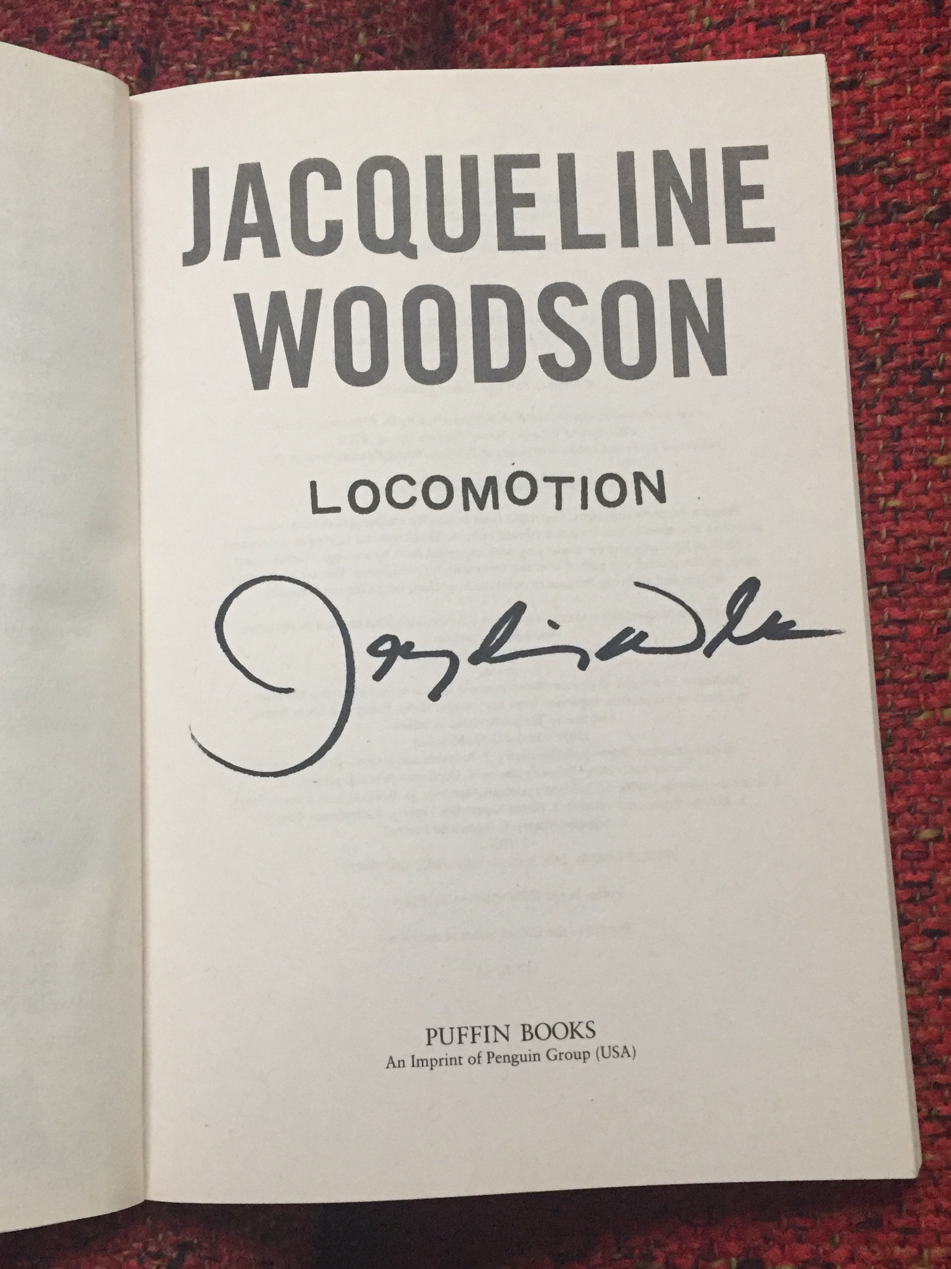 [image description: My signed copy of Locomotion. The photo is an up close of the title page with the author, title, and publisher. The signed part is Jacqueline's signature without any personalization.]