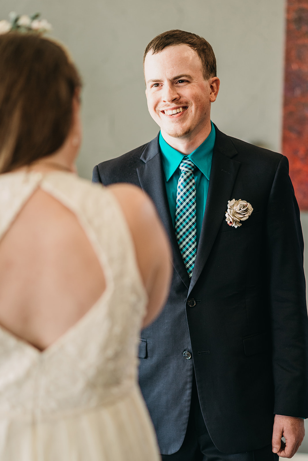[image description: I'm wearing my wedding dress and have my back to the camera. My partner (white, male, average size and build) is wearing a navy blue suit, turquoise dress shirt, and checkered tie. He has a boutonnière made of book pages and is smiling at me.]