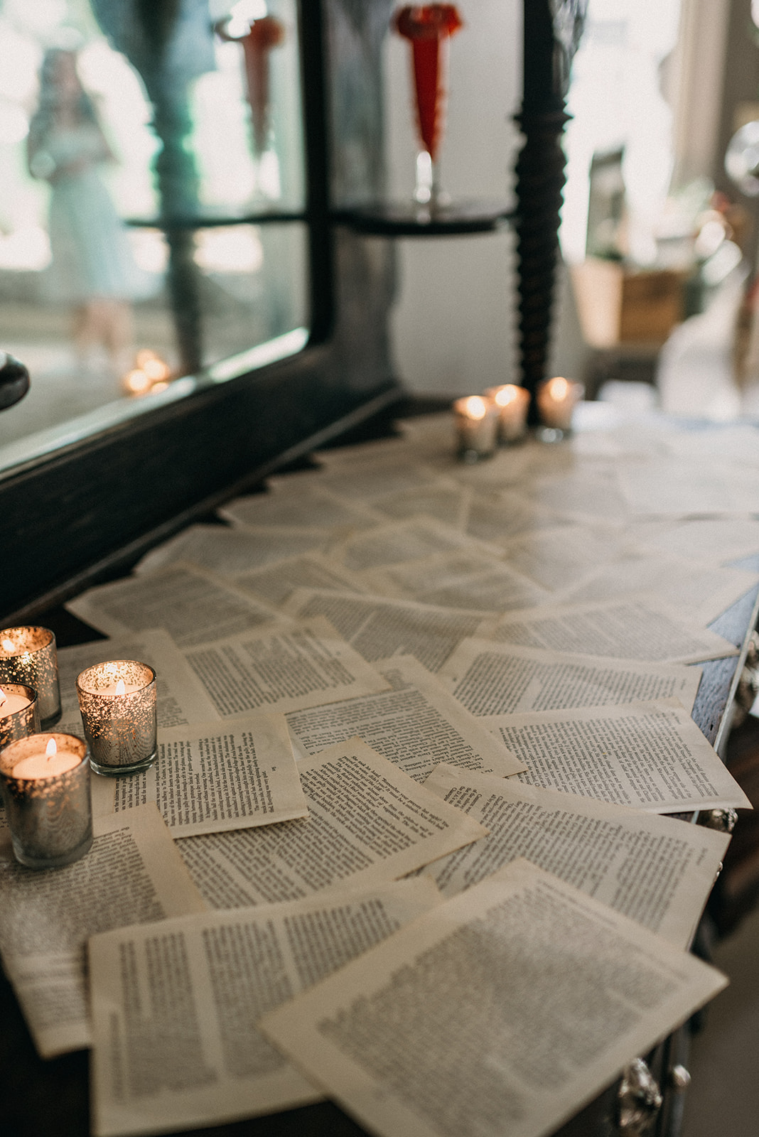 [image descriptions: A close up of the book page table runners and votive candles in silver candle holders.]