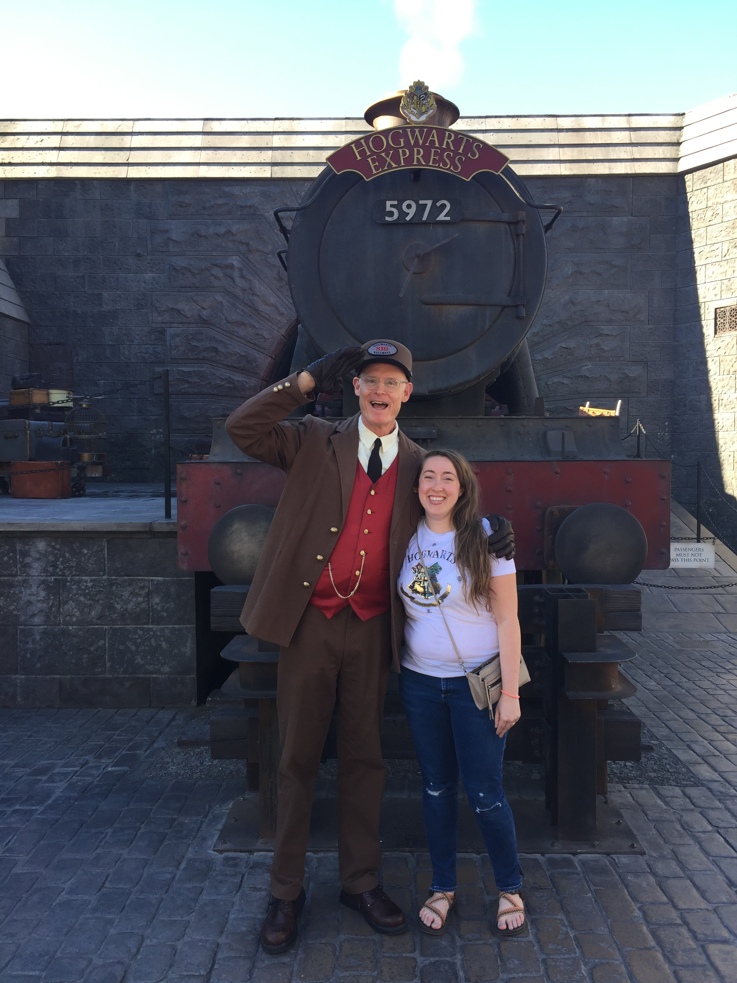 """[image description: a photo of me and the conductor of the Hogwarts Express (an actor, though I wish it were so!). He's a tall white man in a brown suit and red vest with a brown boxy hat. He has one arm around my shoulder and the other is saluting the camera. I'm standing beside him wearing jeans and a white shirt that says """"Hogwarts Alumni"""" and sandals. We're standing in front of the train and smiling at the camera.]"""