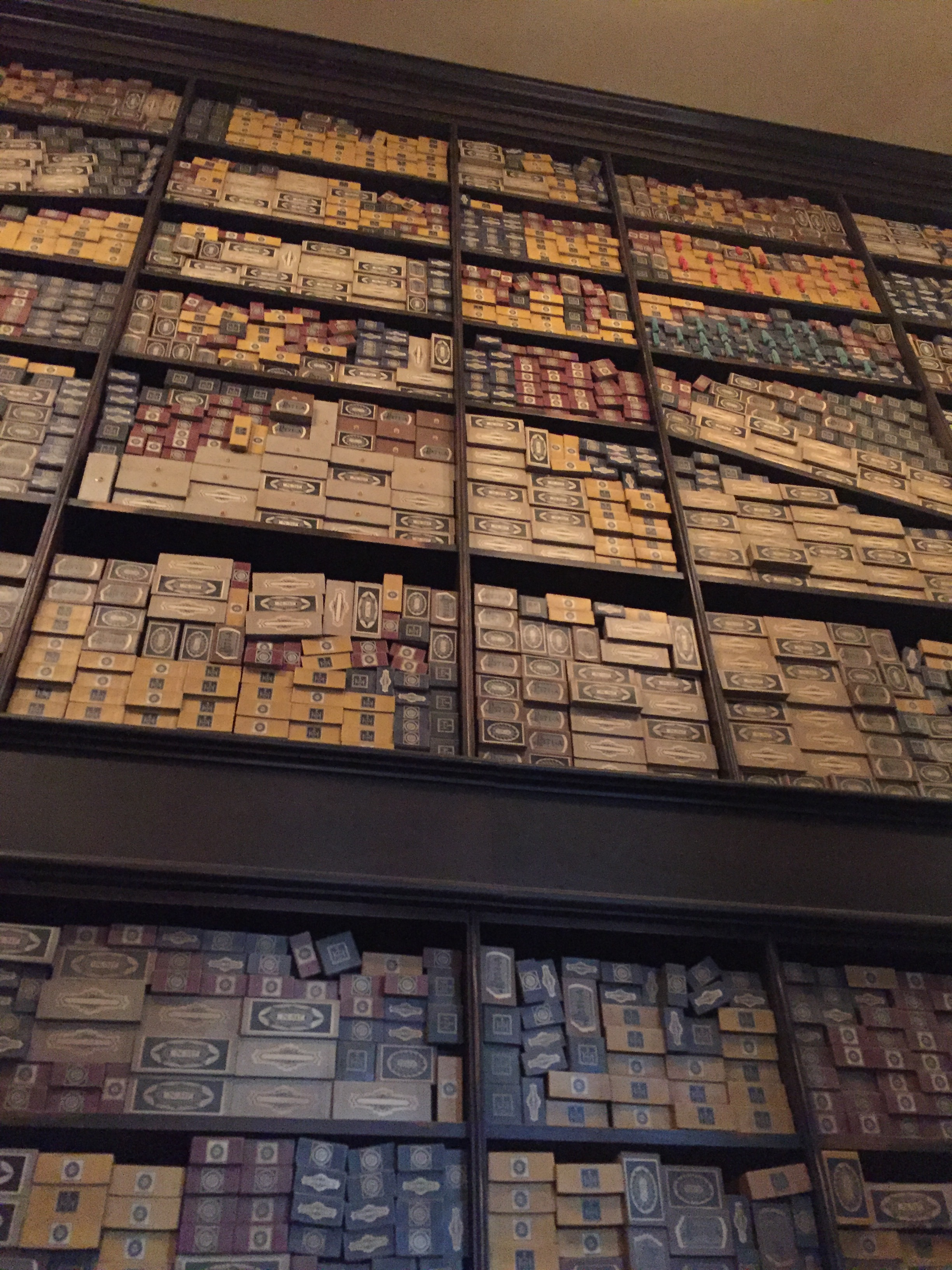 [image description: Inside Ollivander's Wand Shop, there are several walls that are packed floor to ceiling with wand boxes. The wand boxes are long and thin and the boxes are red, yellow, blue, gray, and brown. They all have labels and stickers to seal them, though they're too small for me to read, so I don't know what they say. Sorry!]