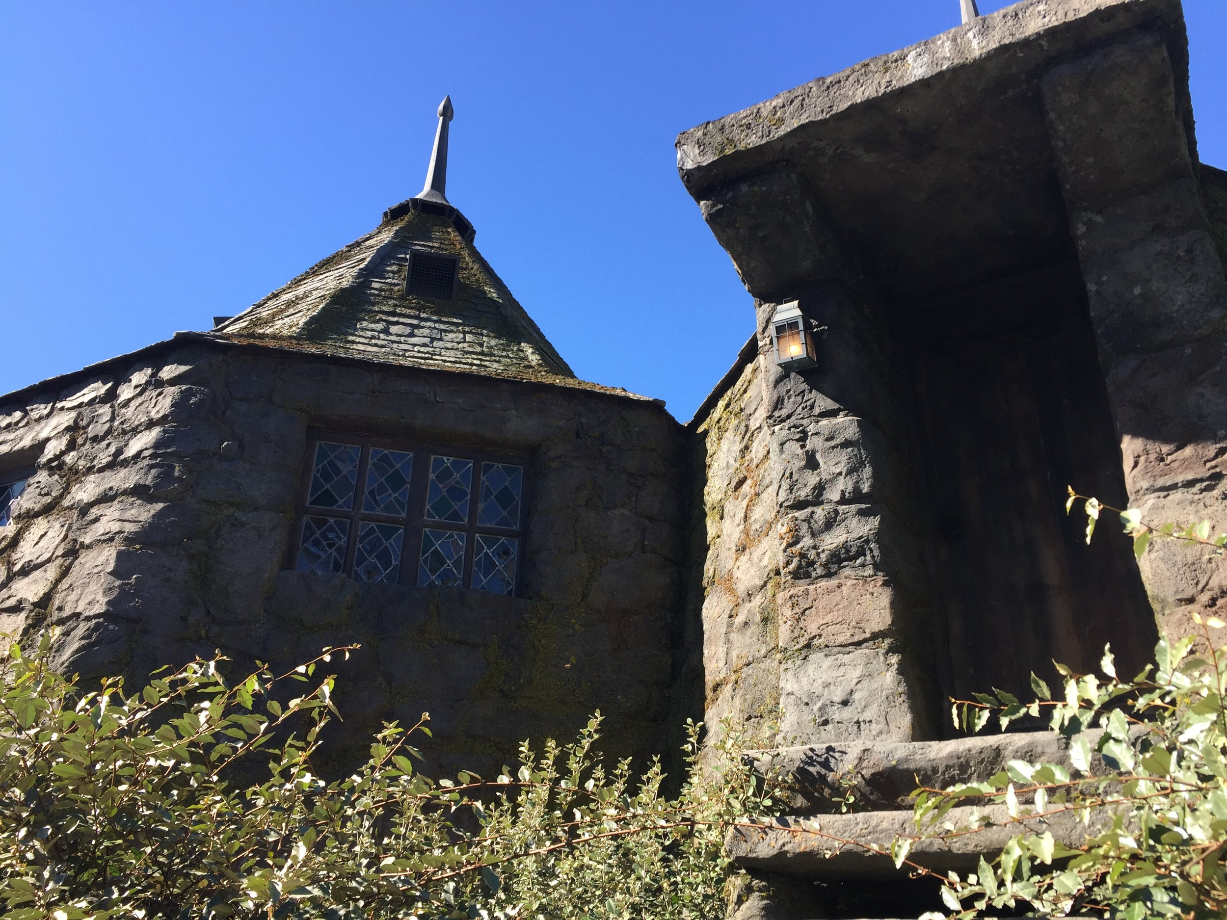 [image description: A life-size replica of Hagrid's Hut. It's a circular stone dwelling with stained glass windows and a large stone entrance with stone steps. The roof slopes upward steeply and has a long spire.]