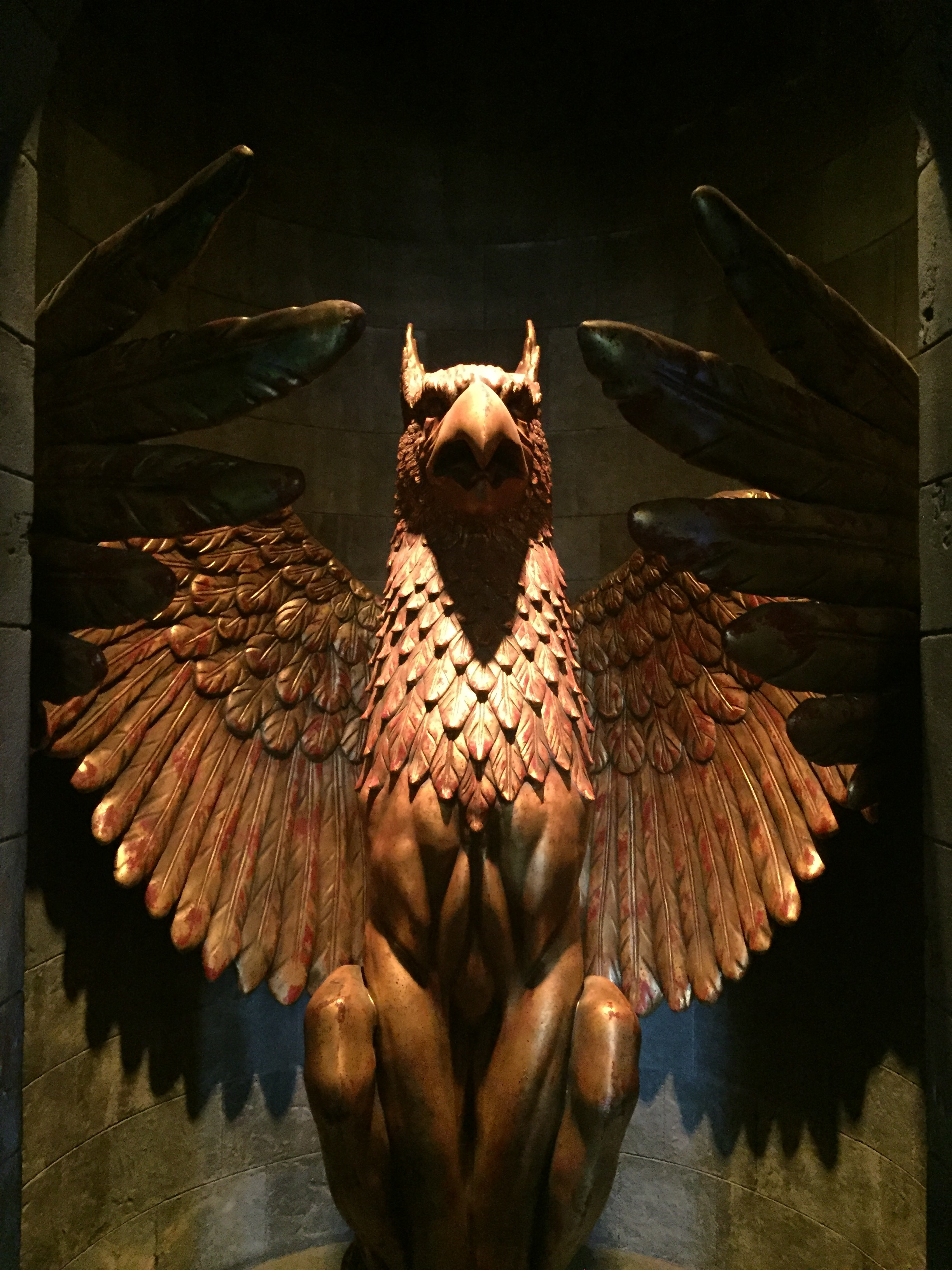 [image description: large, gold phoenix statue surrounded by a circular wall. It's the famed entrance to Dumbledore's office. The phoenix's wings are curved around to mirror the curve of the wall and the bird stares straight ahead, beak slightly open.]