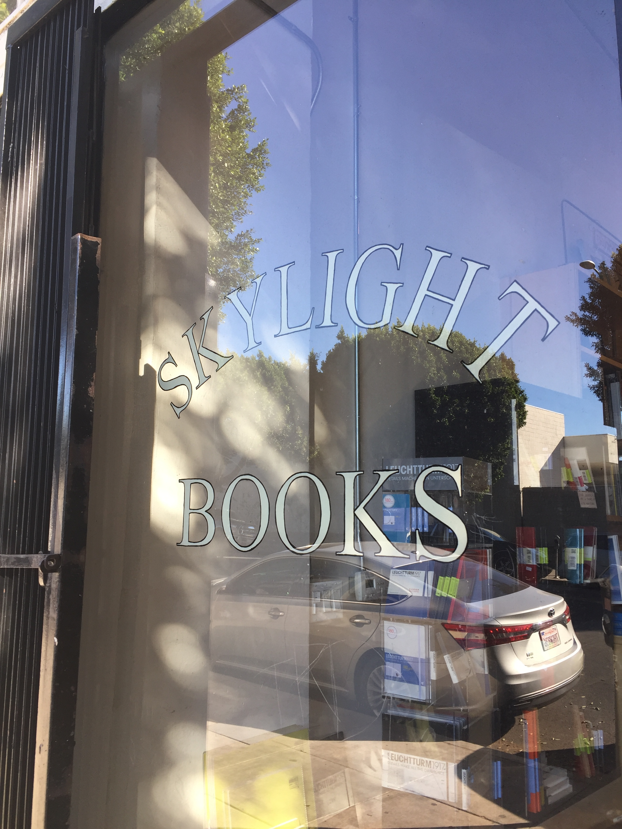 [image description: An up close look at one of the shop windows of Skylight Books. The store's name is painted in a cream color and outlined in black on the window. There's a car parked in front of the store that's reflected in the window.]