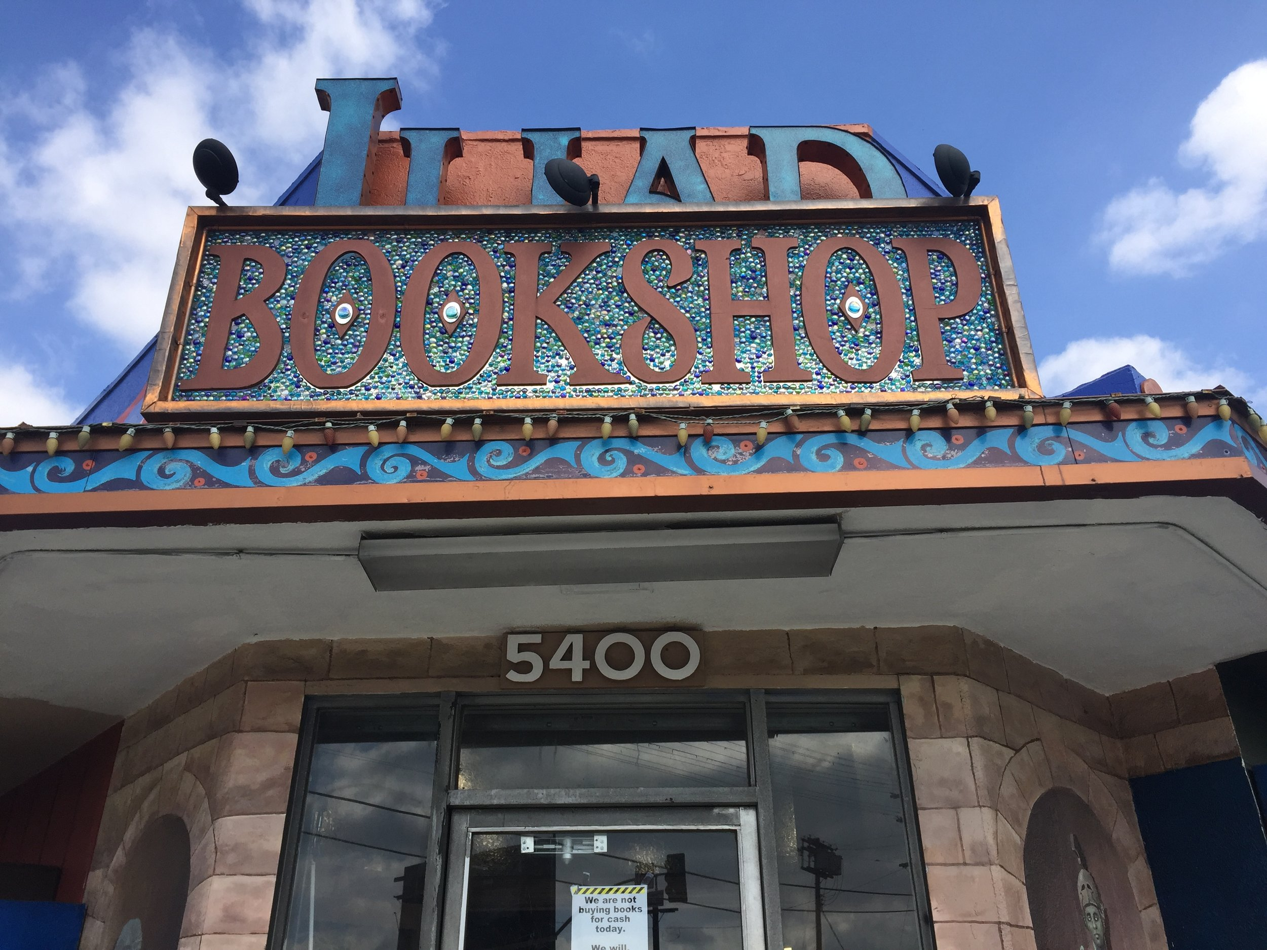 [image description: An up close look at the Iliad Books sign when you enter the store. The store's name is carved out of large blue letters and copper, part of which is on a background of blue mosaic.]