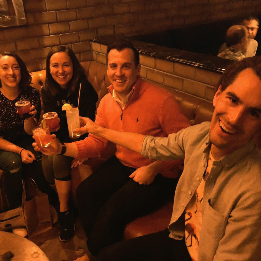 [image description: a group of people sitting on a couch with their cocktails raised. From left to right there's me, Robyn, Kyle, and Ethan. John isn't pictured because he's taking the photo.]