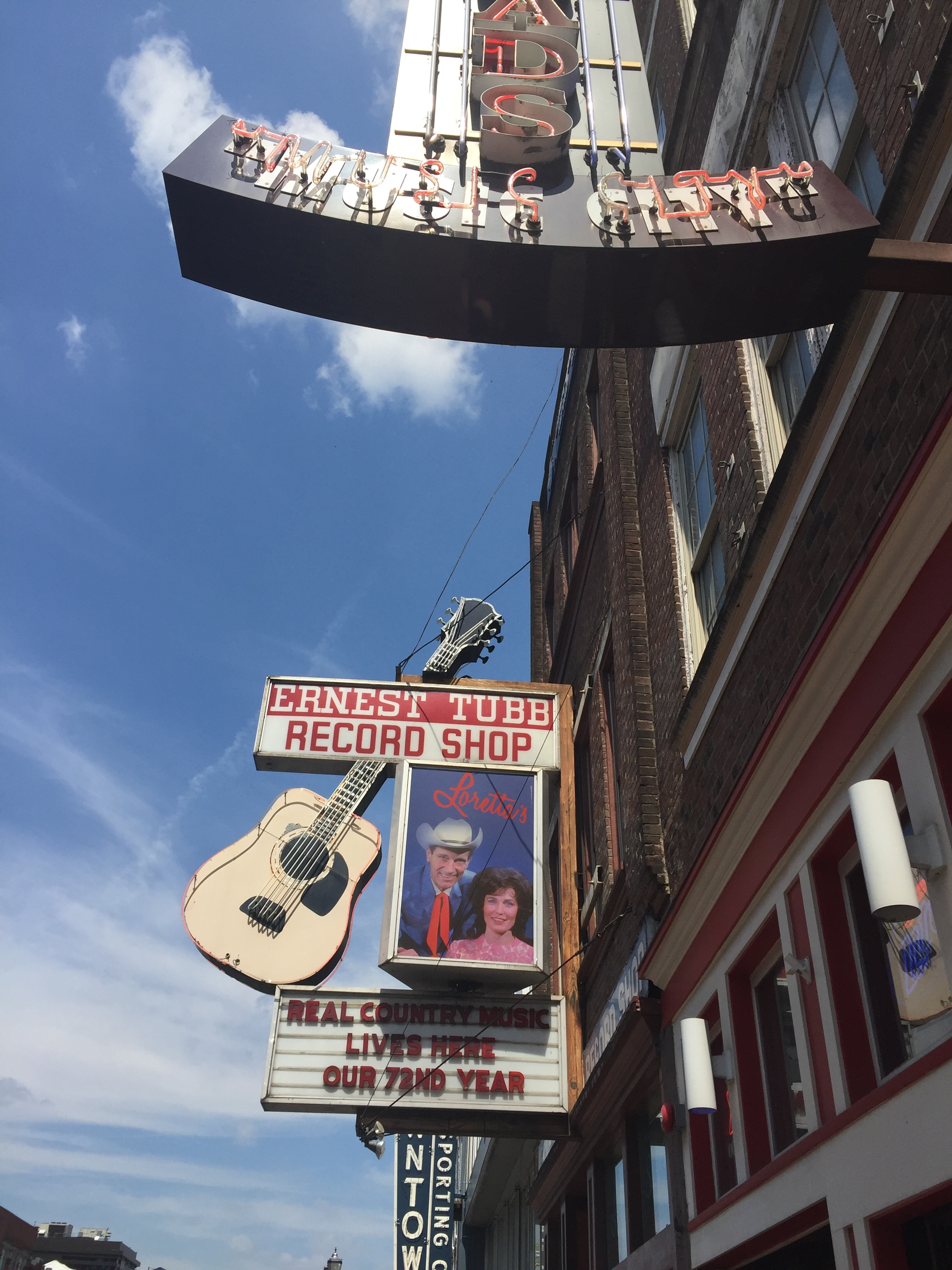 image description: One of the many old signs on the Nashvegas Strip. This one features a neon guitar and a photo of Ernest Tubb and Loretta Lynn. The sign reads: Ernest Tubb's Record Shop. Real country music lives here. Our 72nd year.""