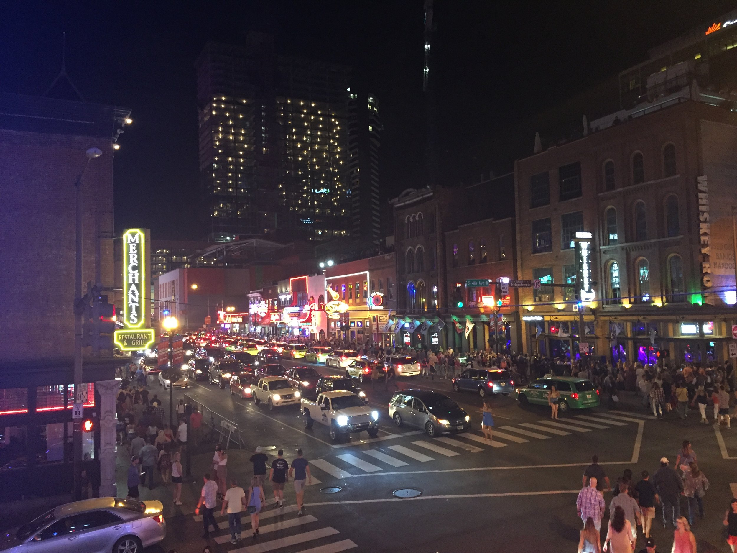 image description: The Nashvegas Strip at night when all the signs are lit up in neon. There's bumper to bumper traffic and the sidewalks are crowded with people.