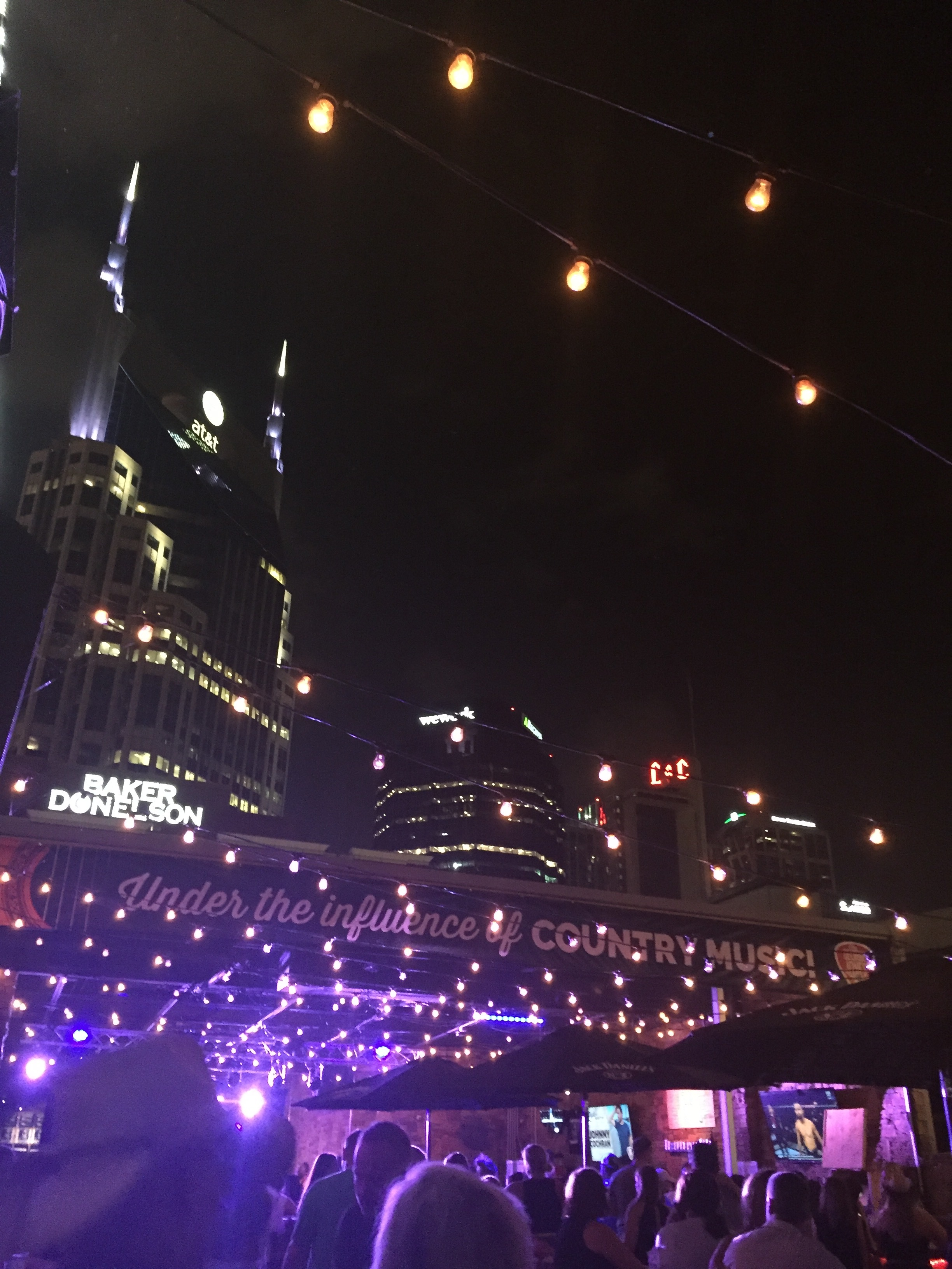 "image description: A portion of the Nashville skyline at night, as taken from the rooftop bar at George Jones' bar. A sign above the stage reads ""under the influence of country music."""