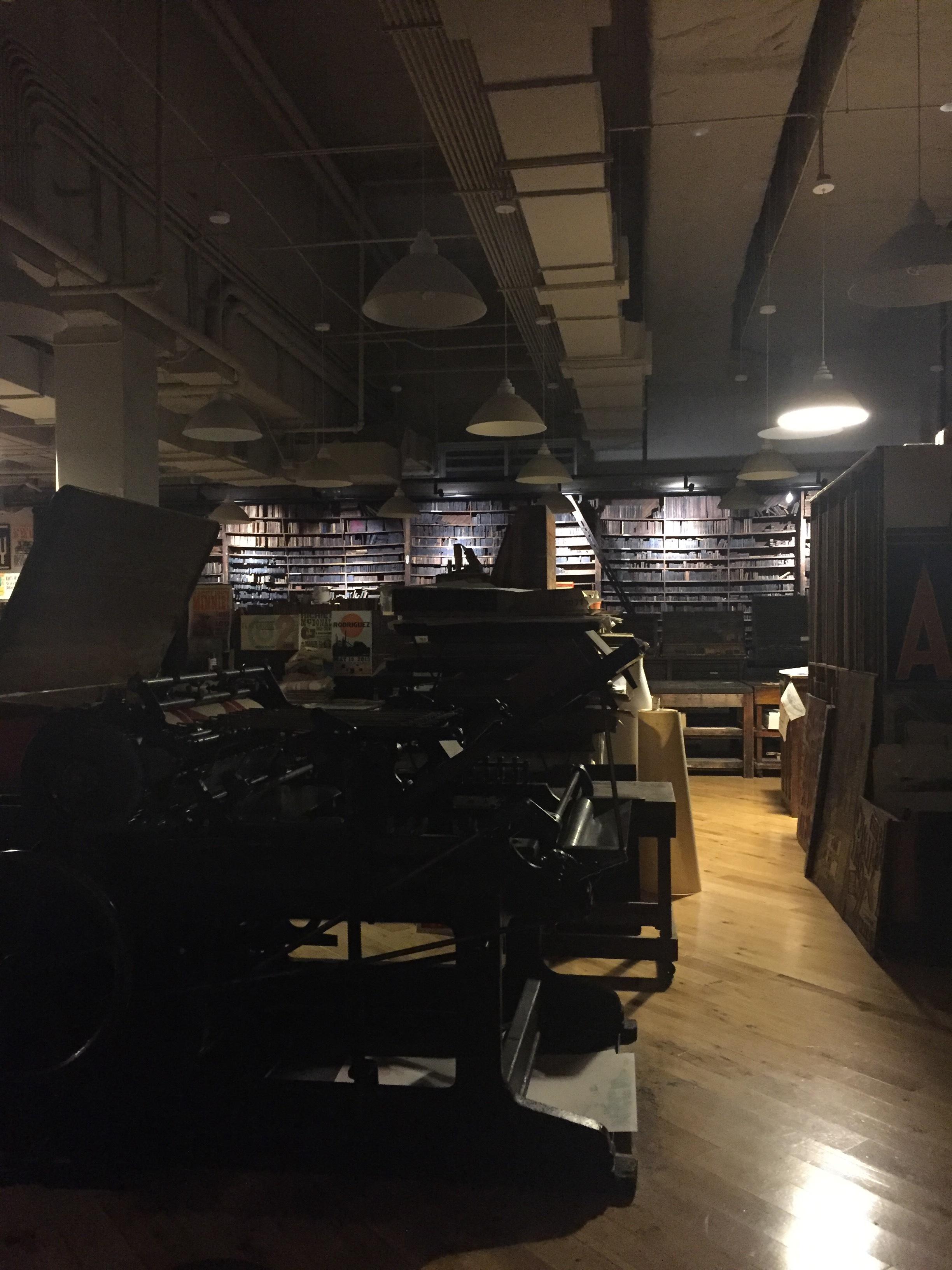 image description: A massive metal letterpress printer in a darkened print shop.