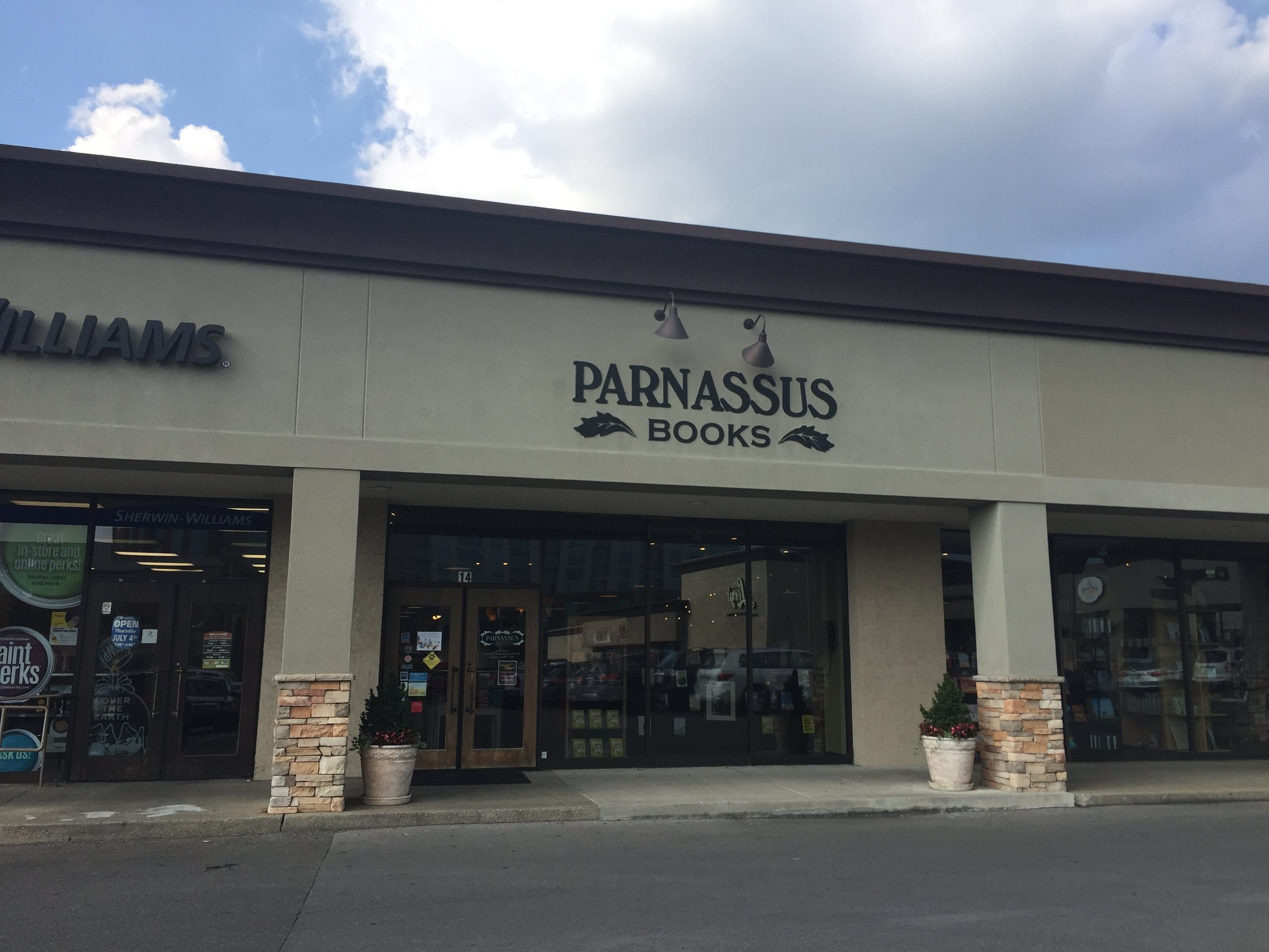 image description: The storefront of Parnassus Books. Suburban strip mall beige and all.