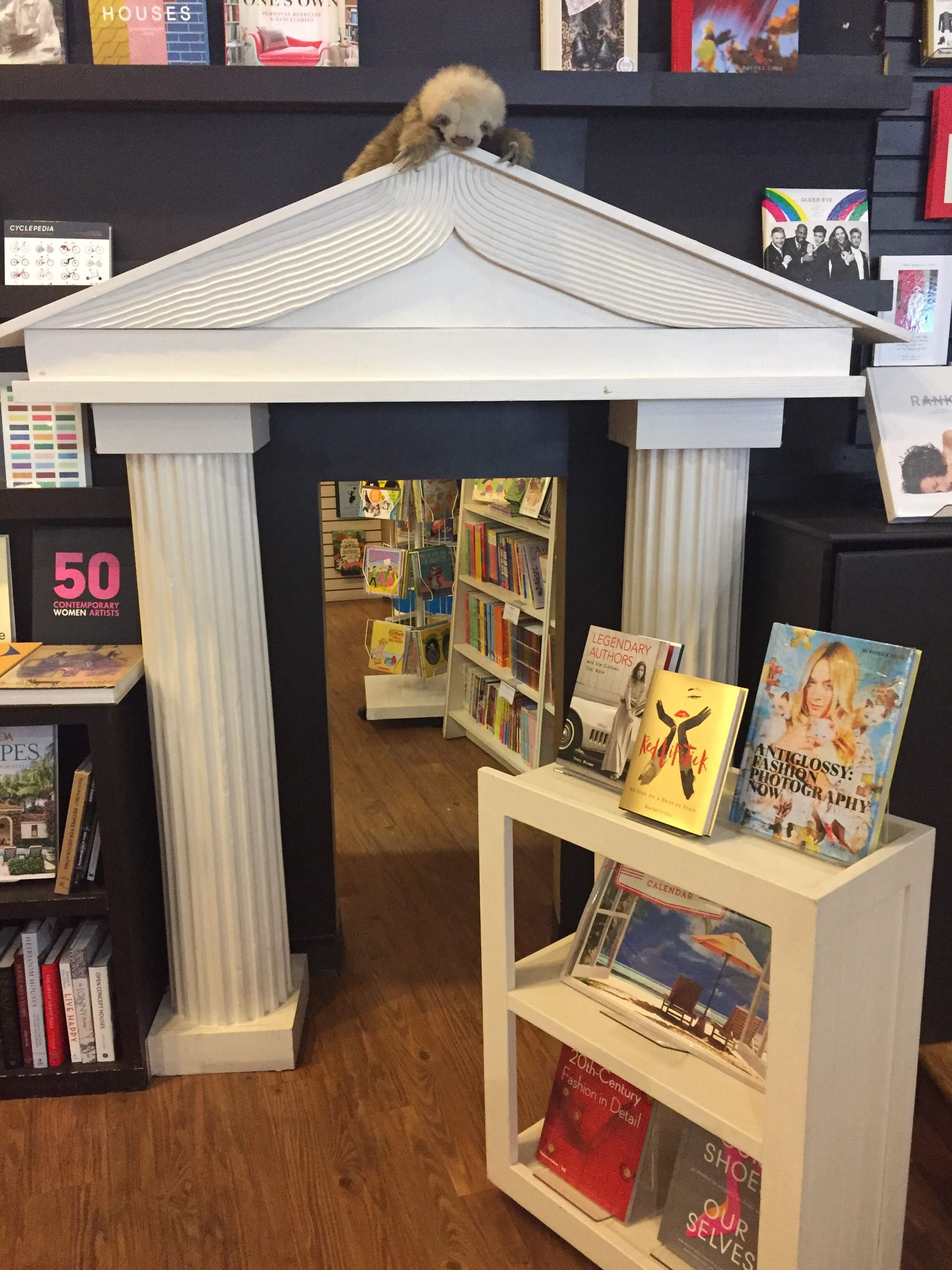 image description: The entrance to the children's section of the store. It has a tiny doorway with Greek columns and a roof styled like an open book.