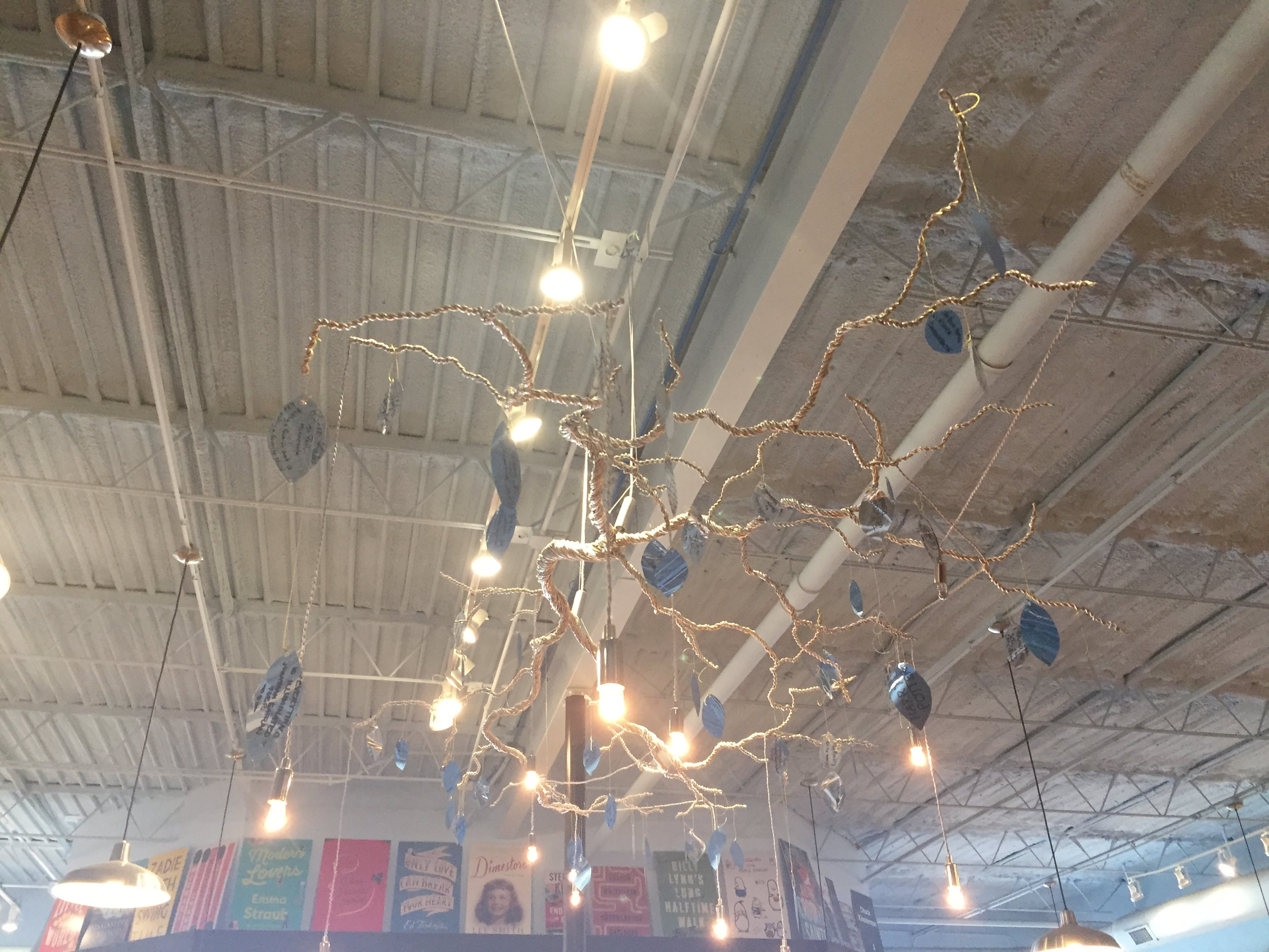 image description: An installation art sculpture hanging from the ceiling. It looks like tree branches and leaves made out of metal. There are writing on the leaves, but it was too small for me to read.