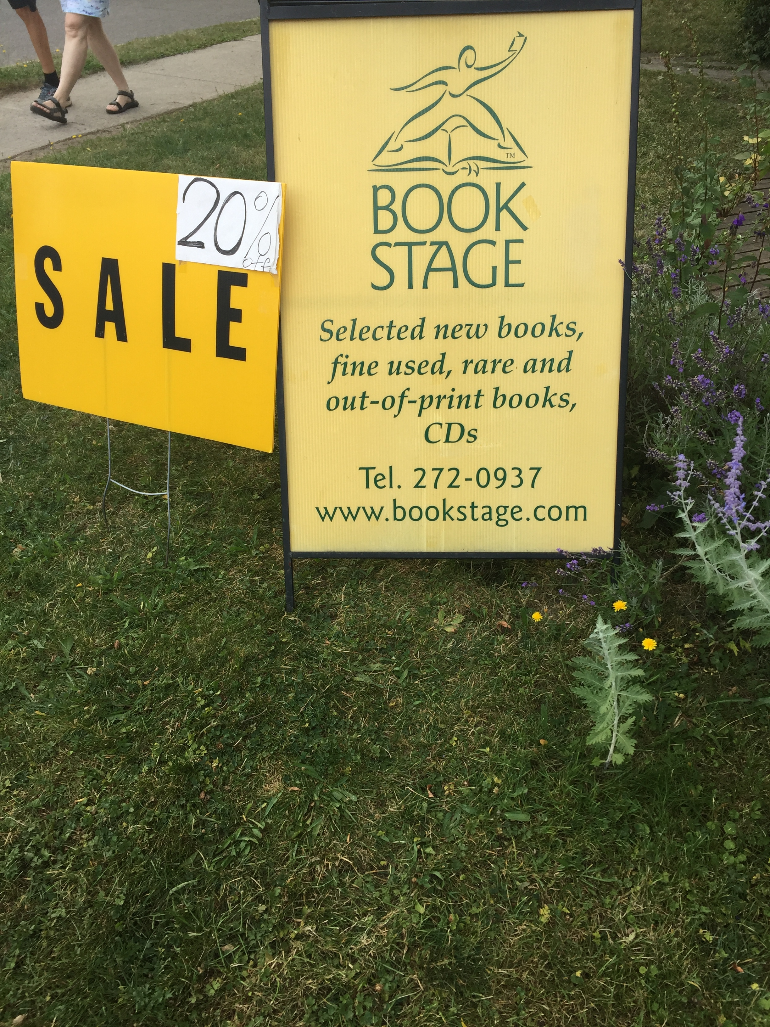 "[image description: A sign advertising the bookstore, Book Stage. It reads: ""Selected new books, fine used, rare, and out-of-print books. Sale 20% off."""