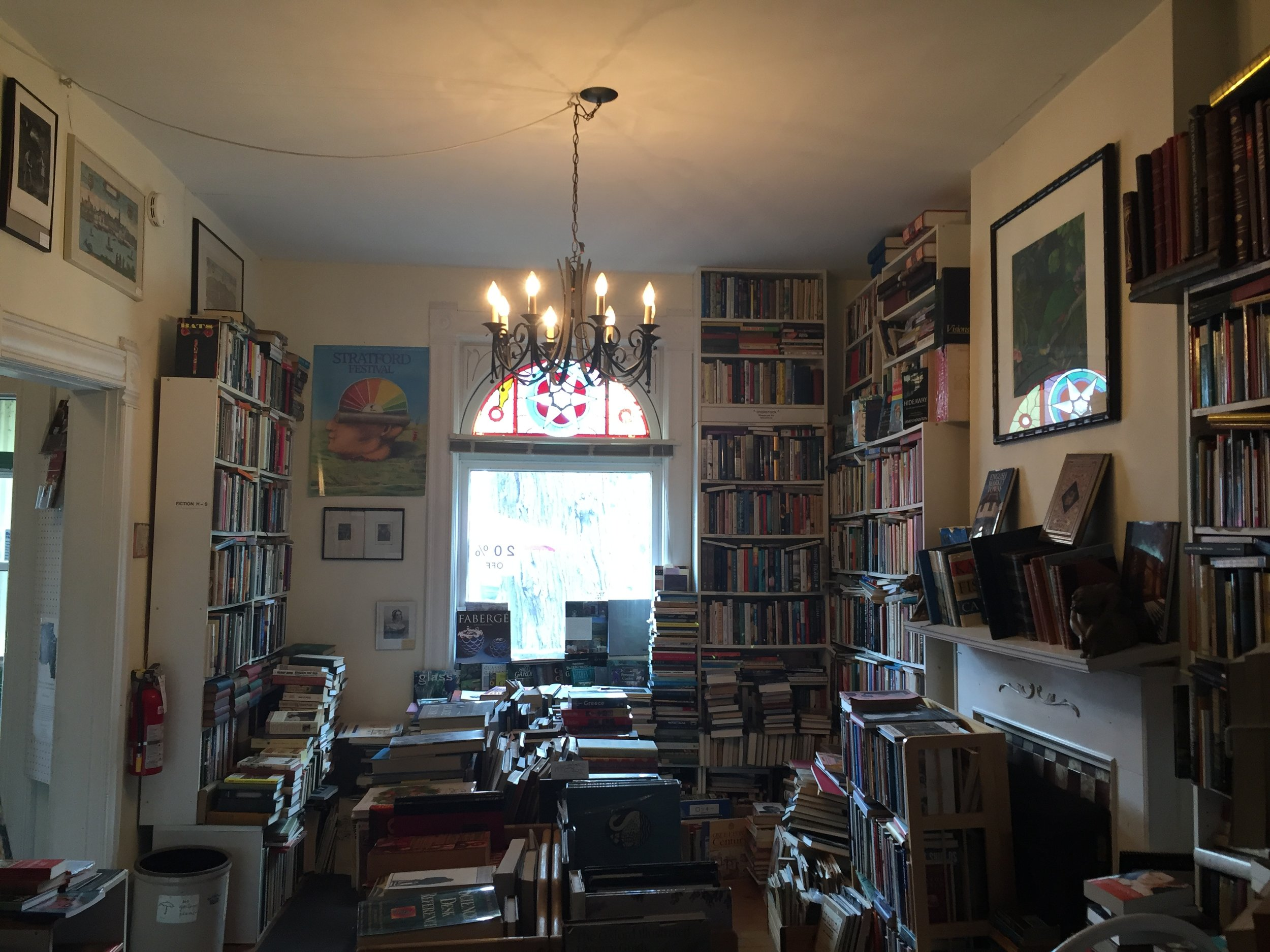 [image description: Inside the Book Stage shop. A view of the main room features floor to ceiling bookshelves, a large window, stained glass, a chandelier, and a fireplace mantle that's about to fall off because of how many books are placed on it.]