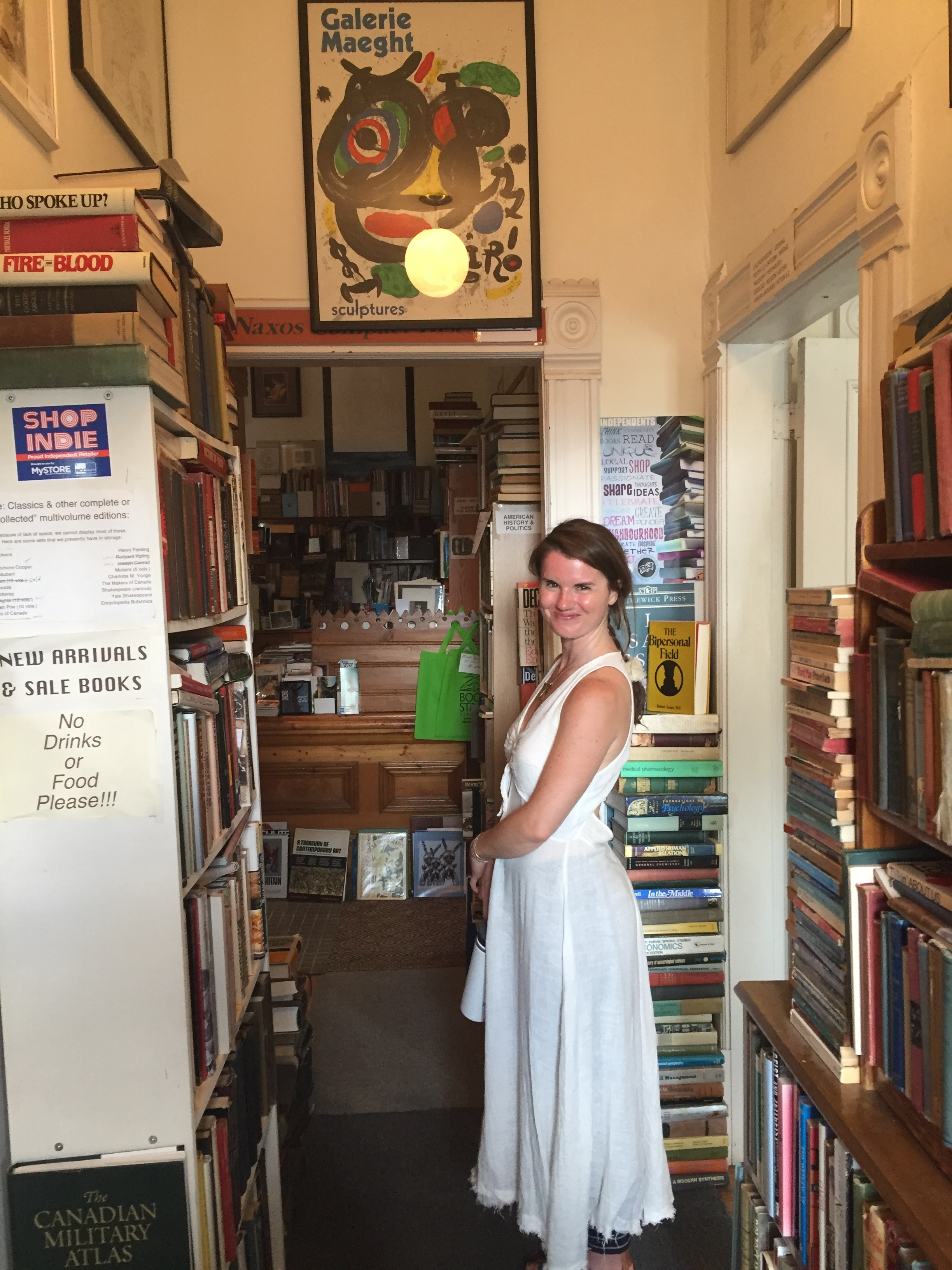 [image description: A photo of my friend Julia amidst the bookshelves at Book Stage. She's a white woman with long dark hair wearing a long white dress. She's a goddess in human form.]
