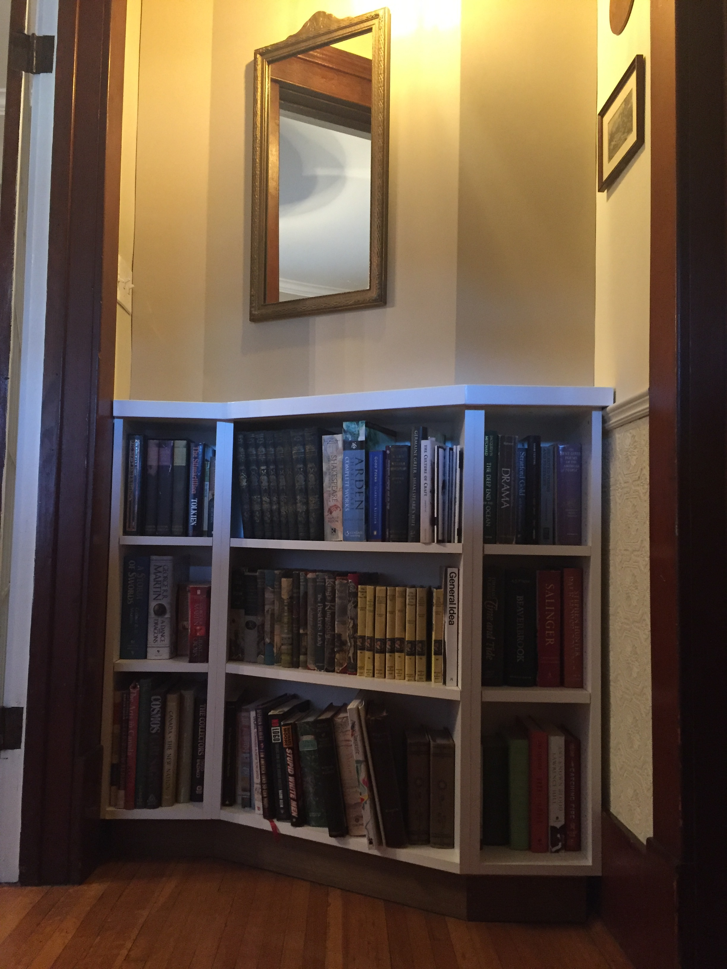 [image description: a small foyer with a curved, Z-shaped wall. A white bookshelf has been custom built to fit the space.]