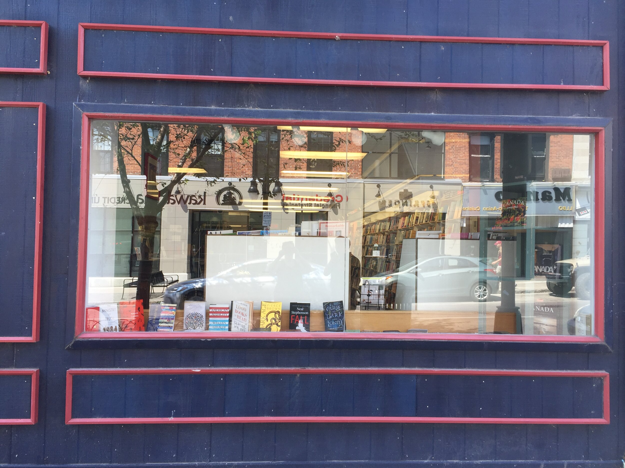 [image description: The display window at Novel Idea bookstore. There are just a couple of books sitting on the window sill; no decorative display.]