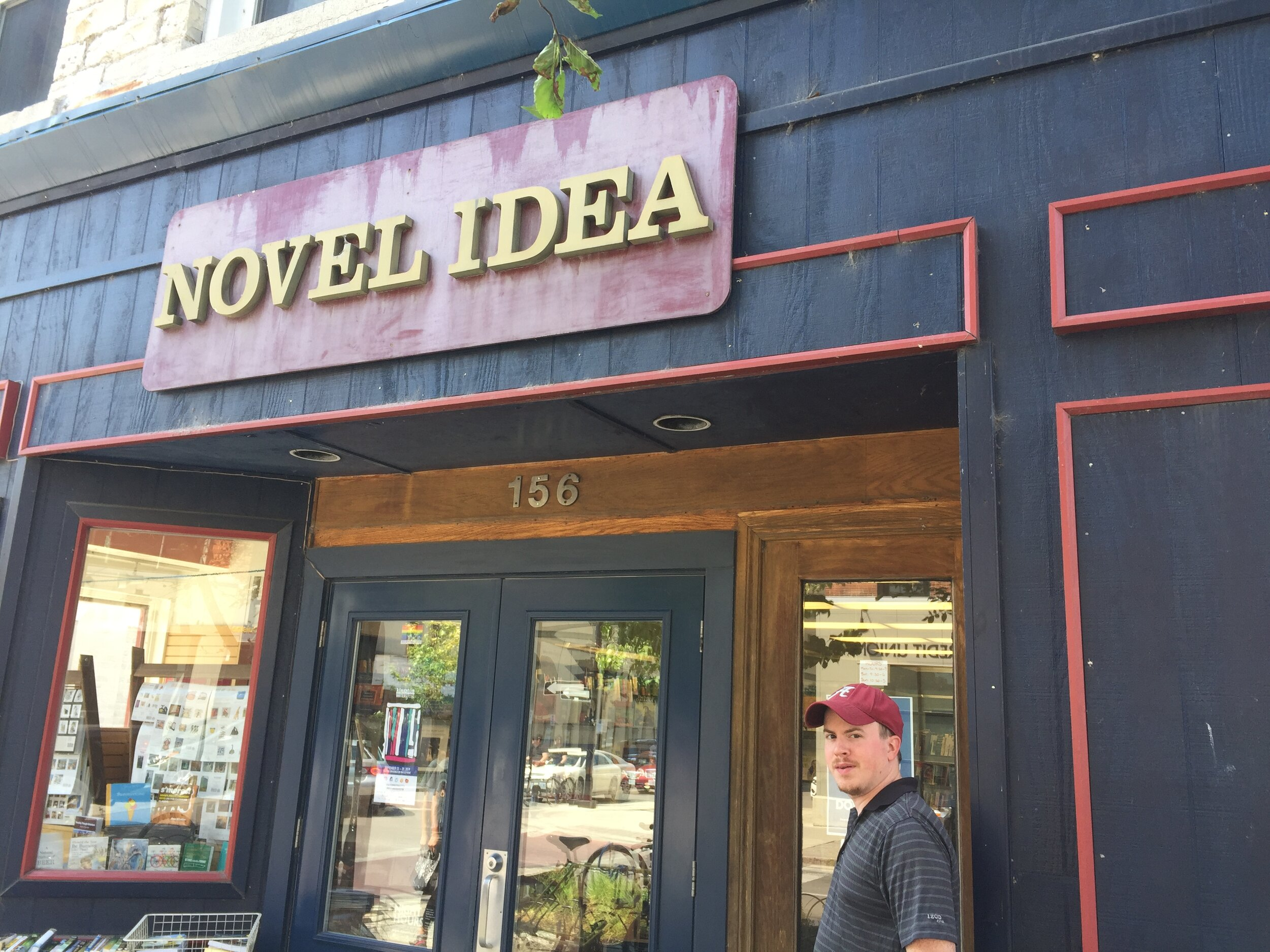 [image description: A picture of my husband, who I affectionately call Mr. Off the Beaten Shelf, in the doorway of Novel Idea. He's a white man in a gray striped shirt and red baseball cap.]
