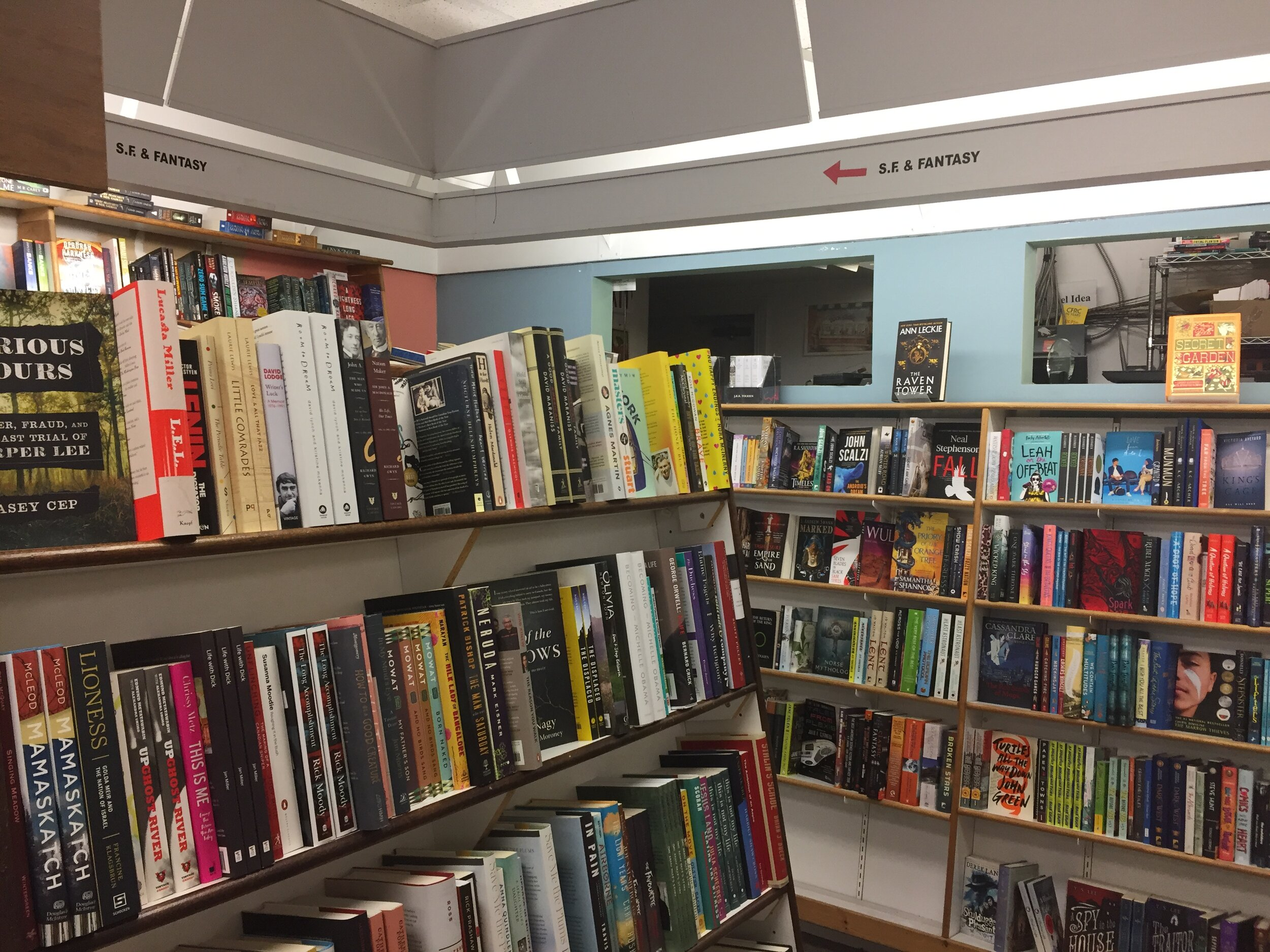 [image description: An inside look at Novel Idea. Large white bookshelves packed to the brim with books in every genre. And the bookshelves are the nice slanted ones that make browsing so much easier.]