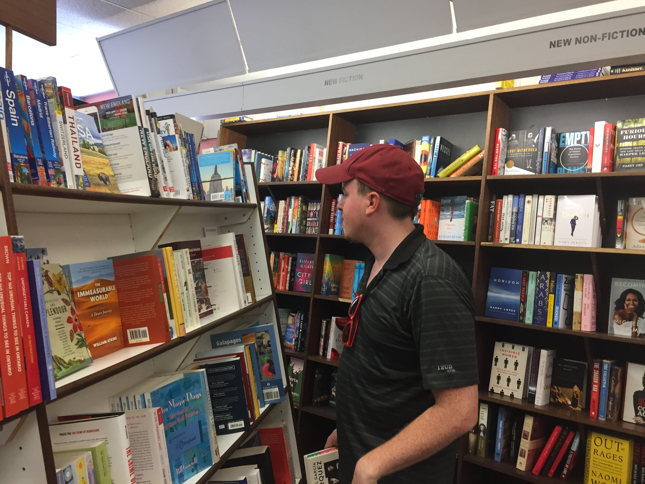 [image description: My husband browsing the travel section of Novel Idea.]