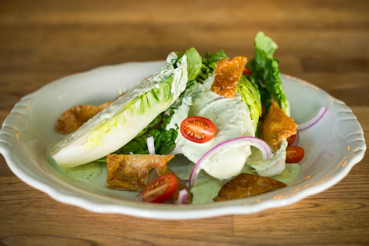 LITTLE GEM WEDGE SALAD                                                                                                                                                                                                                                                         Green goddess dressing, crispy chicken skin croutons, red onion, cherry tomatoes