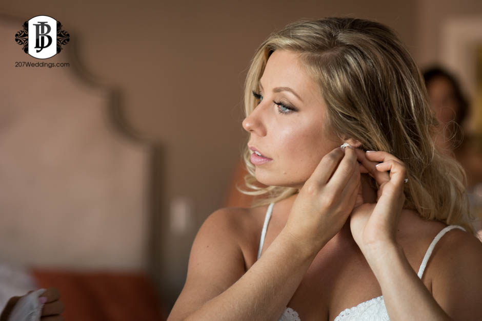 A bride putting her earrings on as she prepares for her wedding, taken by her Maine wedding photographer