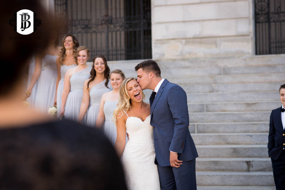 A groom kissing his bride's cheek as they pose with their bridal party on stone steps as the mother of the bride looks on, taken by their Maine wedding photographer.