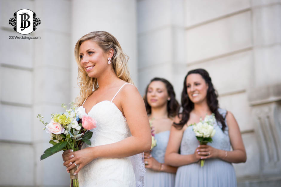 A bride posing for a photo to the side with her bridesmaids in the background, taken by her Maine wedding photographer.