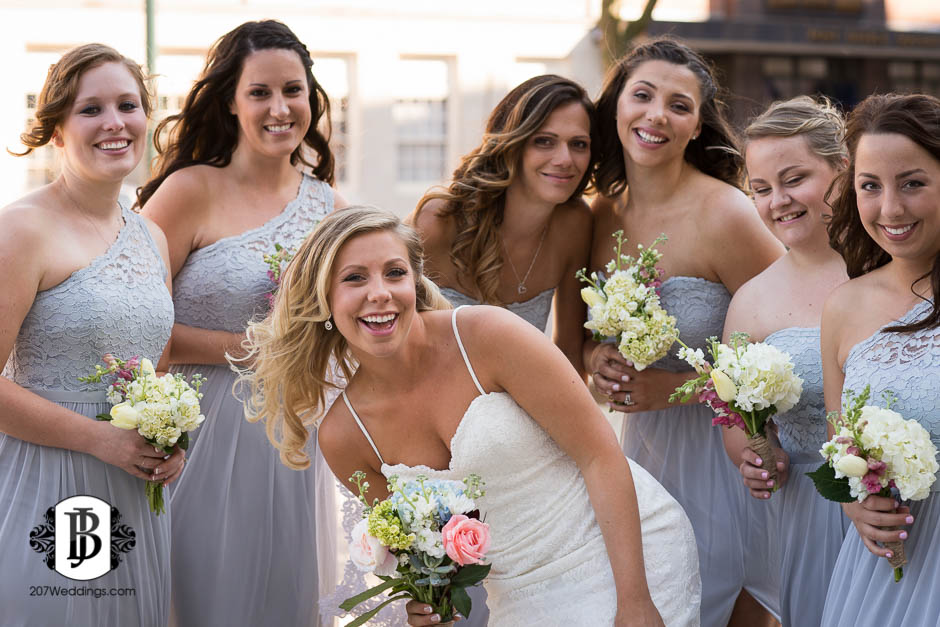 A bride and her bridesmaids posing for the camera, taken by her Maine wedding photographer.
