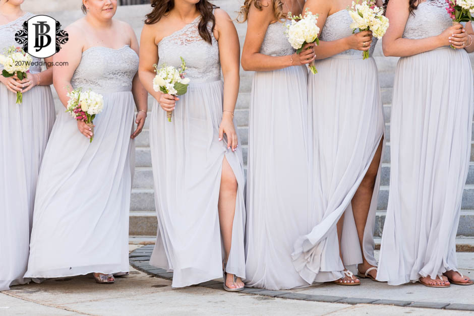 A Maine wedding photographer's photo of a bridal party's flowers and dresses standing together