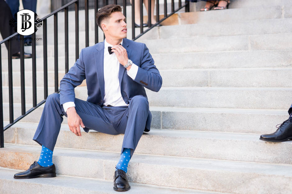 A groomsman sitting on stone steps straightening his bowtie while looking off to the side, taken by the couple's Maine wedding photographer.